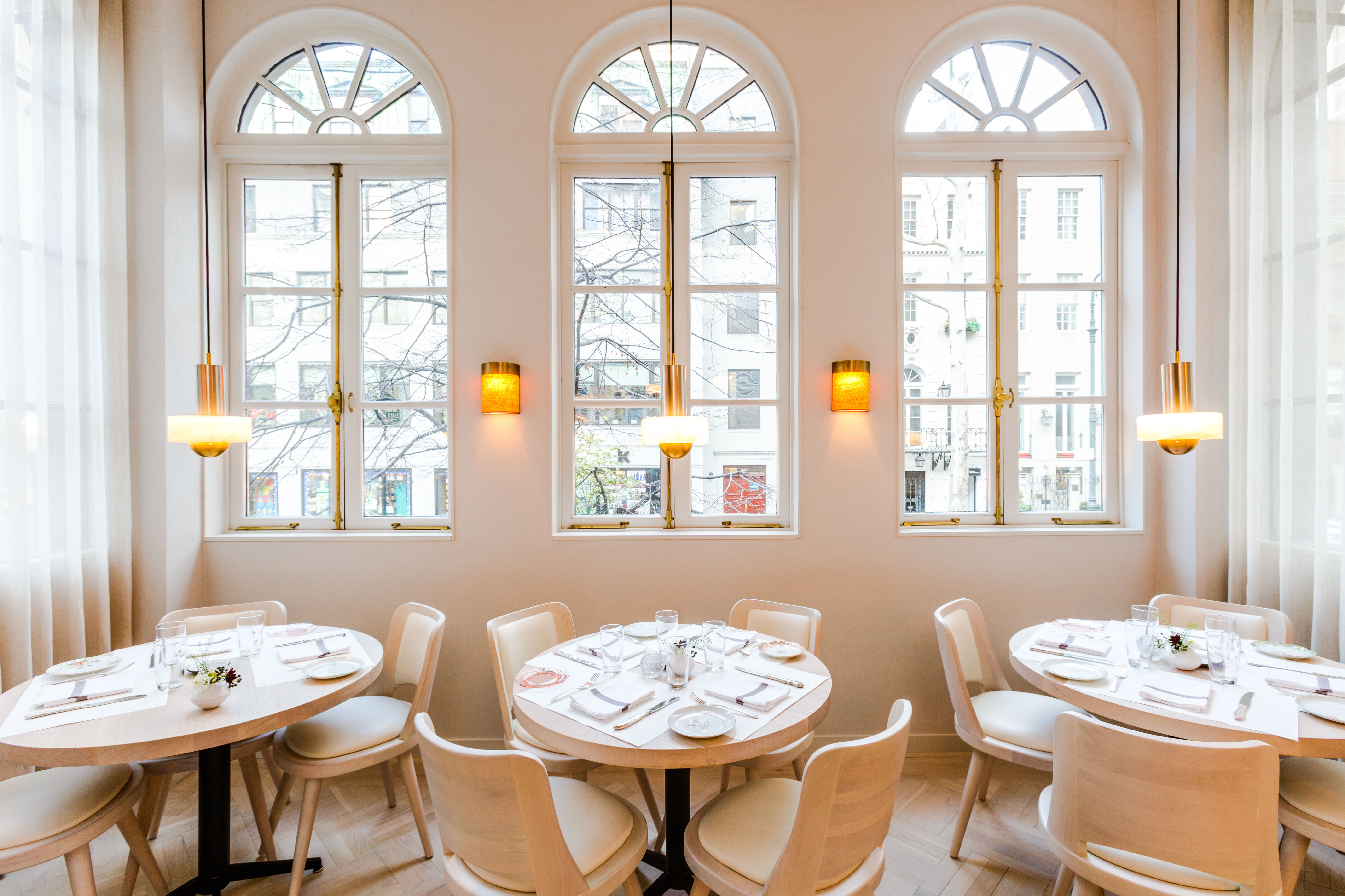 A cream-colored room with three windows and three round tables