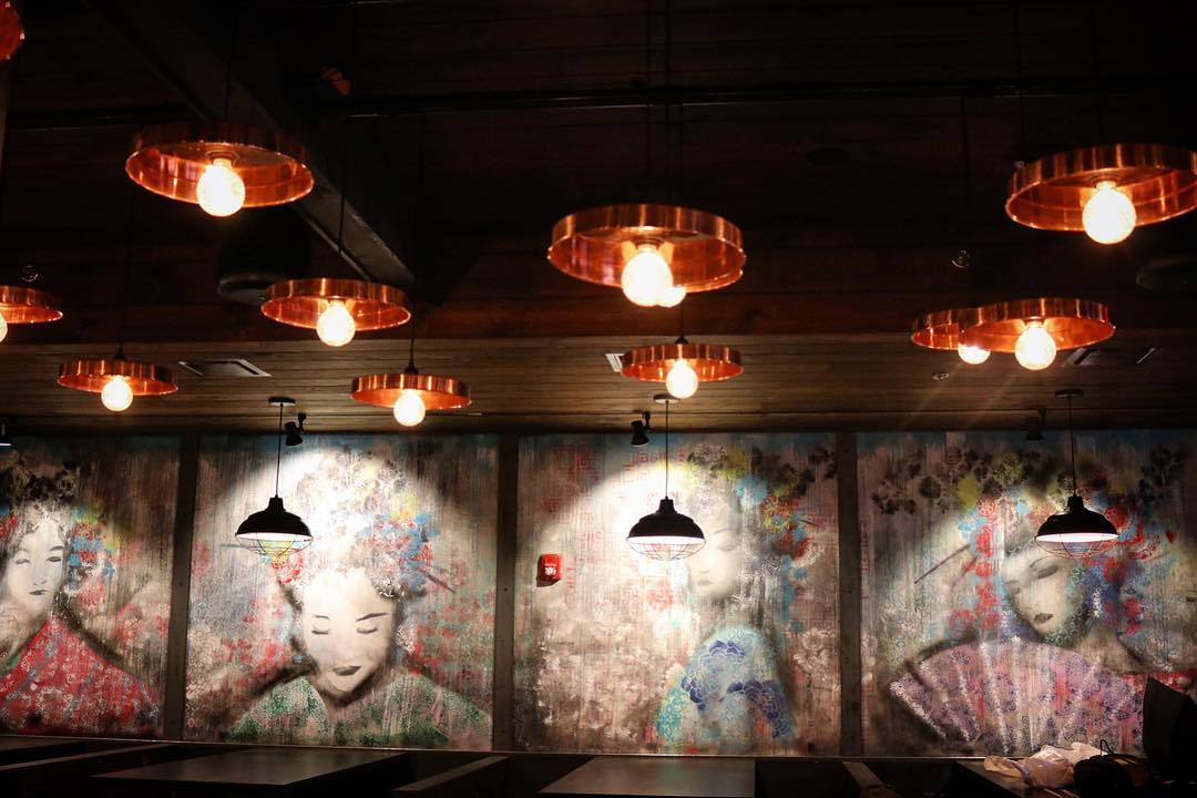 A restaurant interior features a wall mural with Japanese-inspired art. Overhead, there are copper light fixtures.