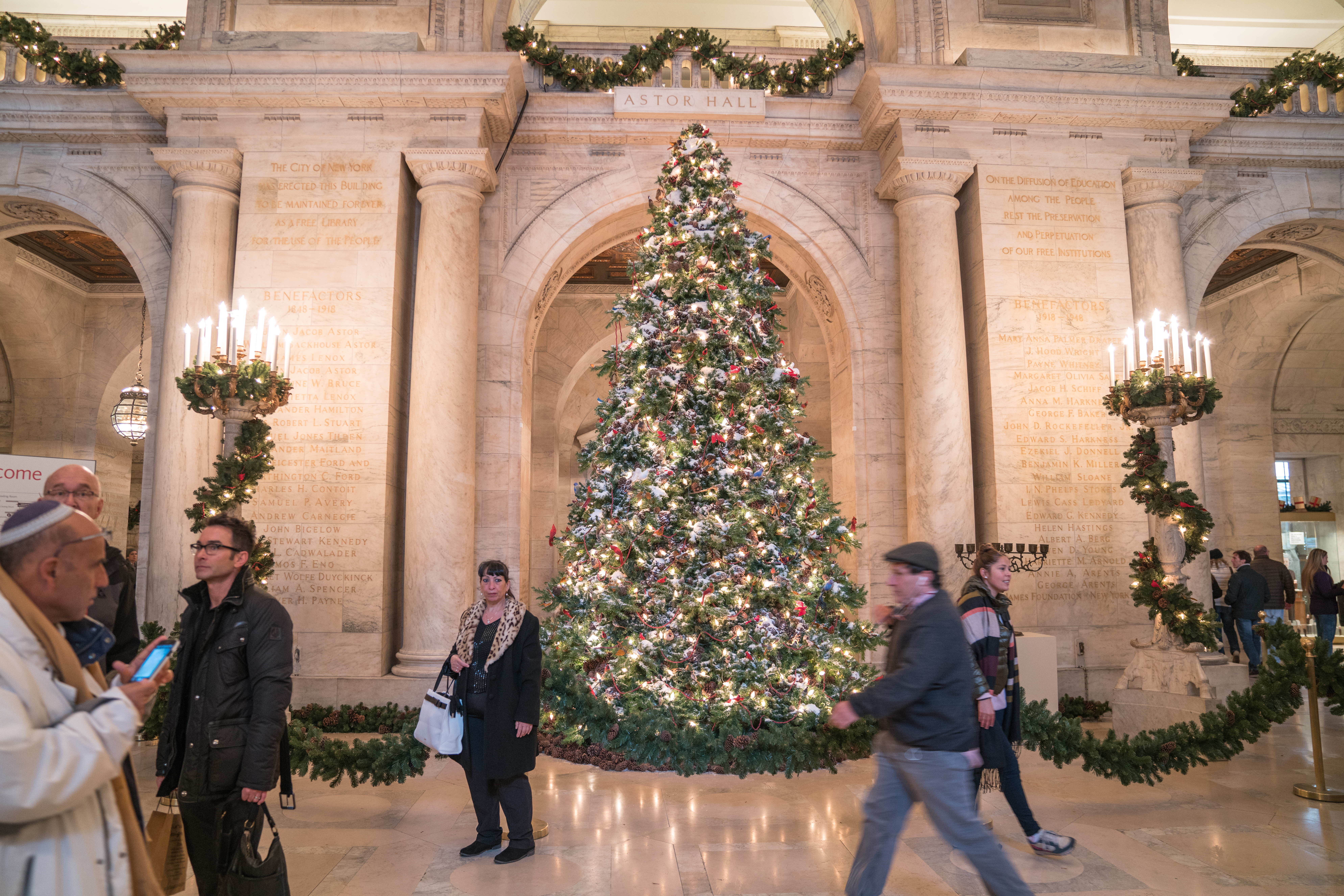 The New York Public Library Christmas tree. There is a wall behind the tree which is tan brick with an archway. There are people walking in front of the tree.