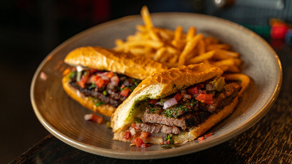 A tri-tip sandwich at Martino's on a plate with a side of fries