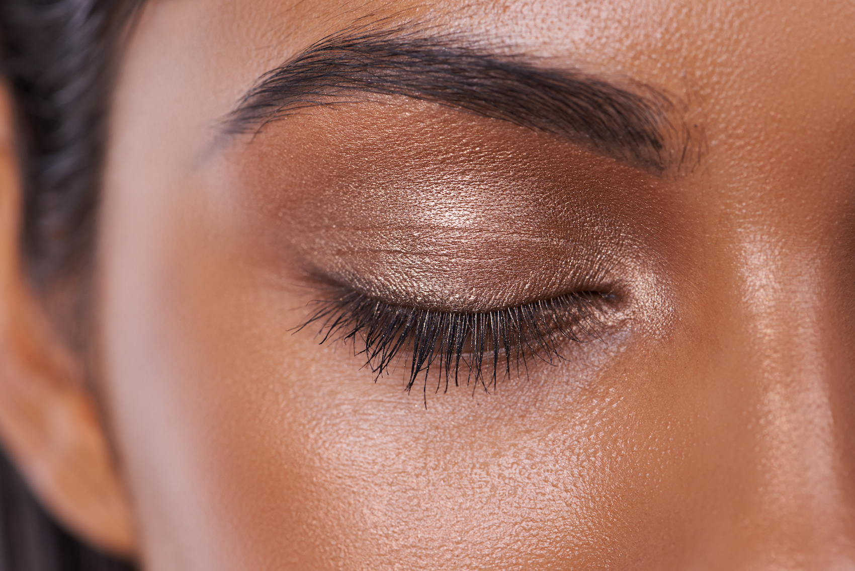 A close up of a woman's eyelids and eyebrow wearing shimmer makeup
