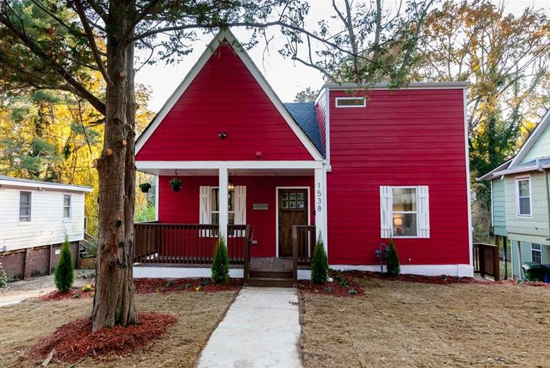 Red bungalow with landscaped yard and sidewalk.