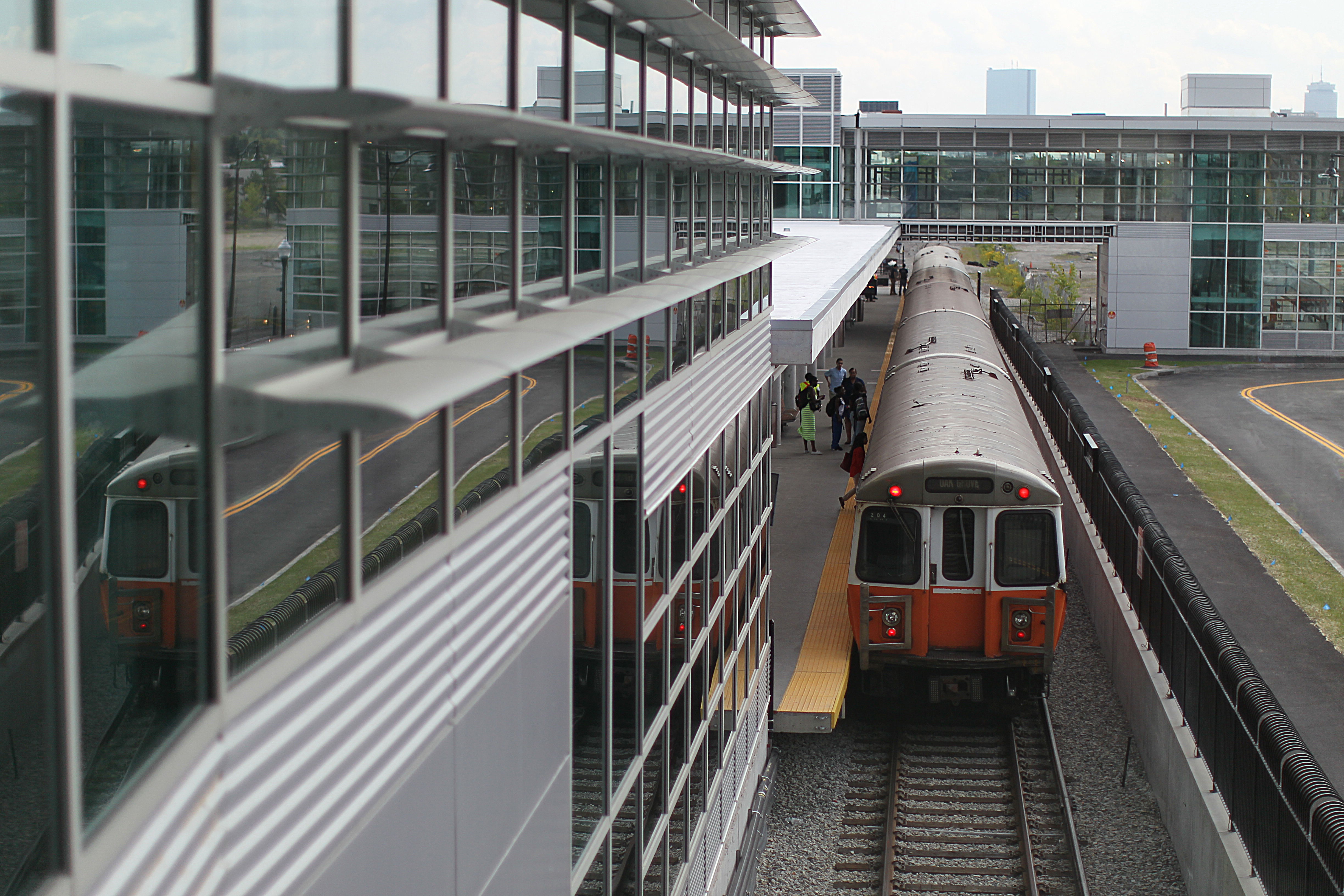 A subway train pulling away from a tall, glassy station.