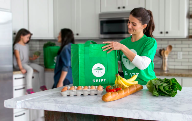 A Shipt delivery person unpacks groceries in a customer's kitchen as a mother and child are seen in the background.