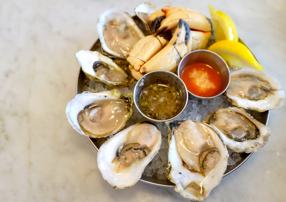 Overhead view of a round metal ice-filled dish holding oysters on the half-shell, crab claws, lemon wedges, and sauces.