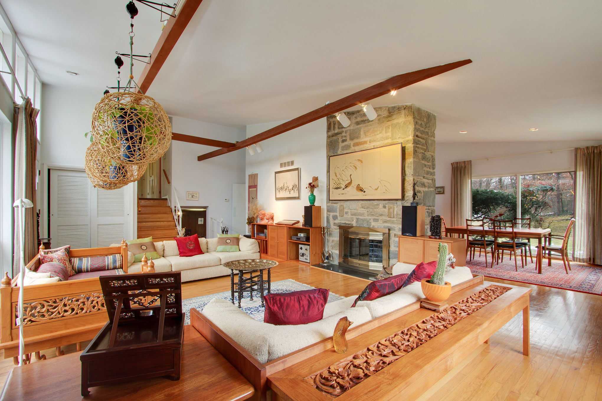 A large living room with vaulted ceilings, a wall of windows, a floor-to-ceiling fireplace, and exposed beams.