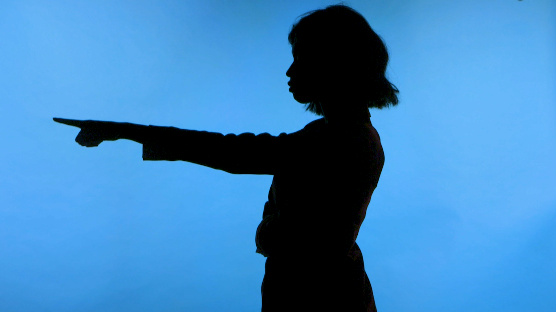 A silhouette of a woman pointing