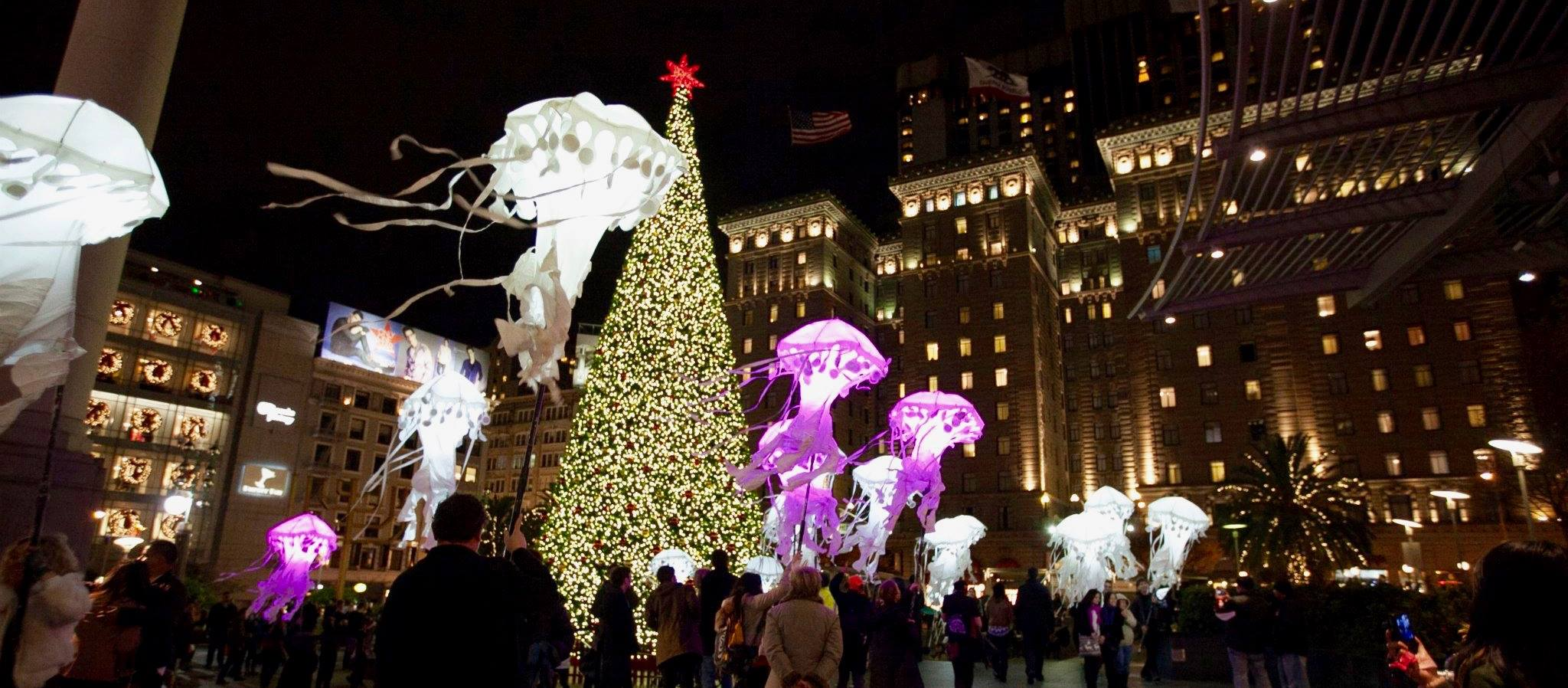 Jellyfish puppets waving in front of the giant Christmas Tree in Union Square.