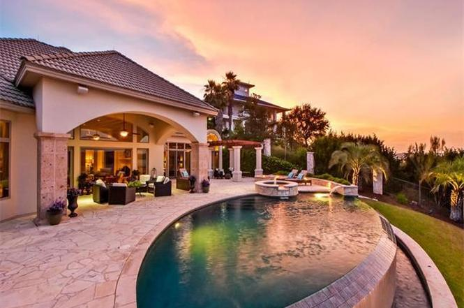 Twilight shot of back of McMansion with pool overlooking lake