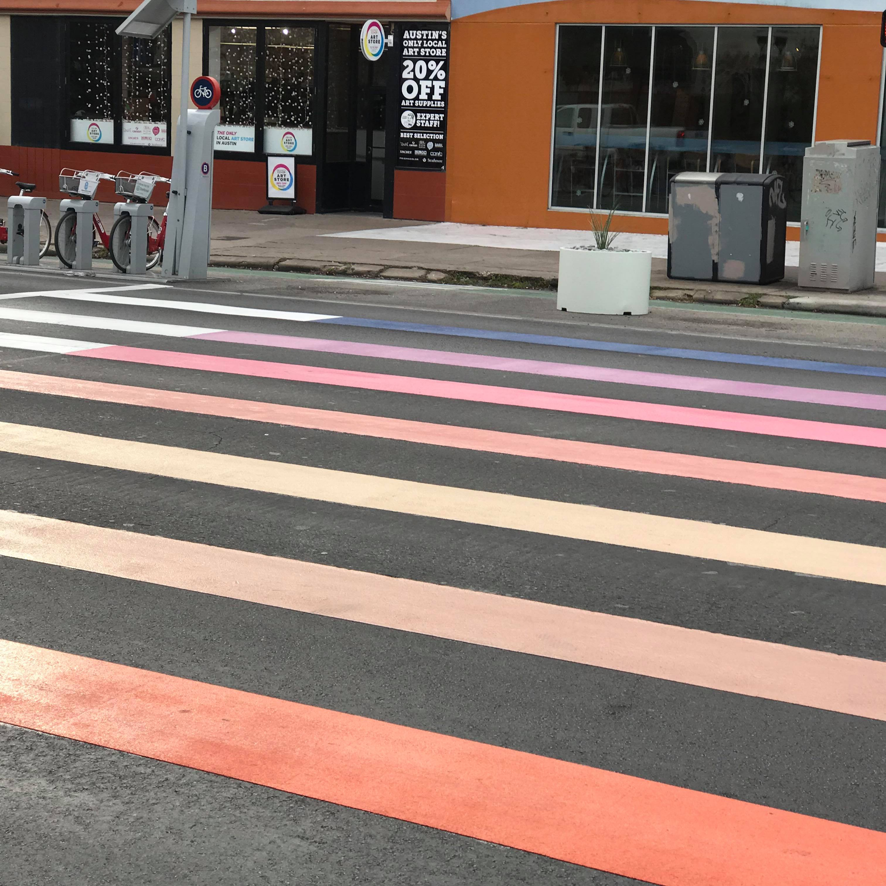 Colorful stripes (not a rainbow) on a street crosswalk