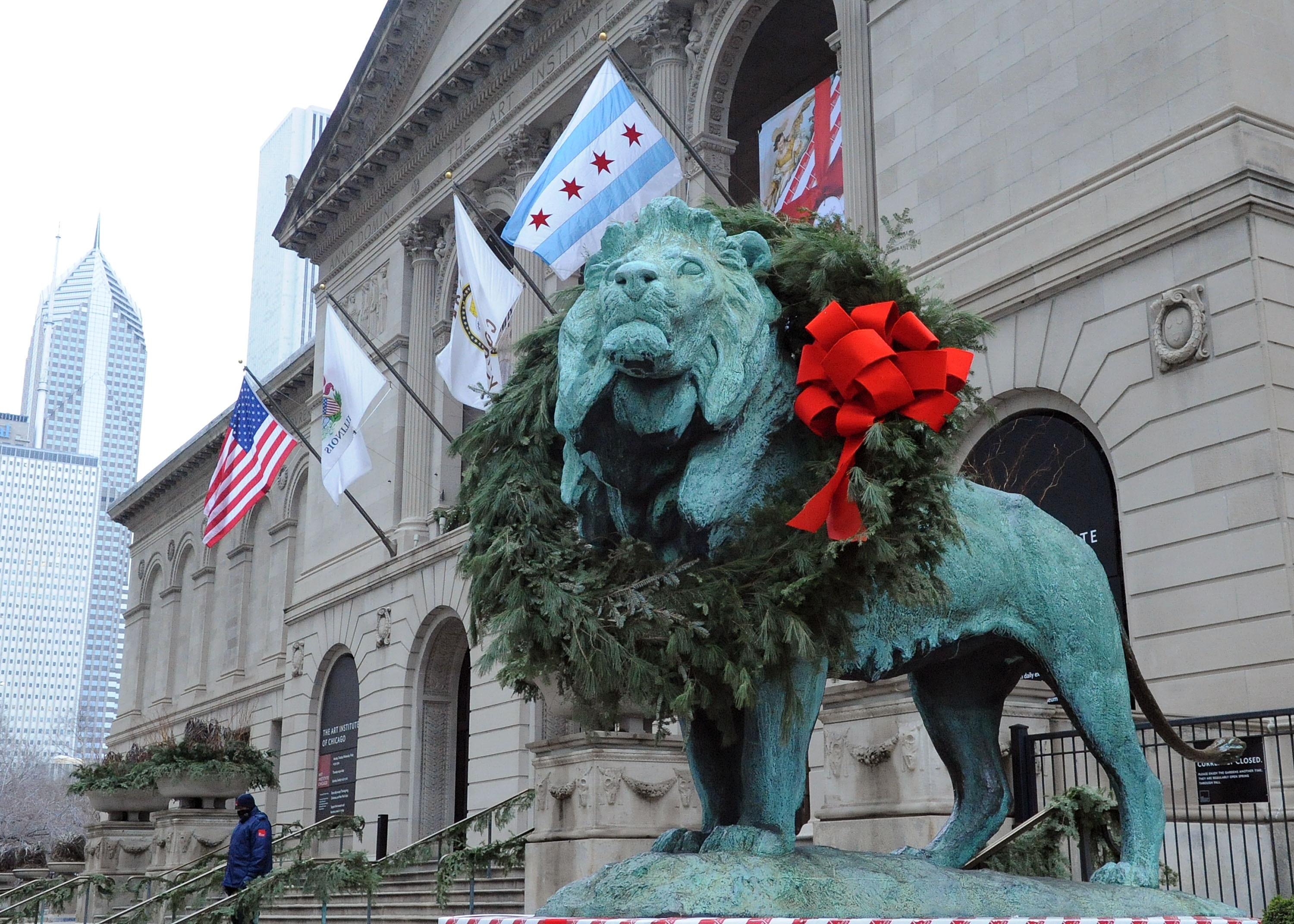 Patina lions at the Art Institute's front entrance with giant evergreen wreaths and red bows.