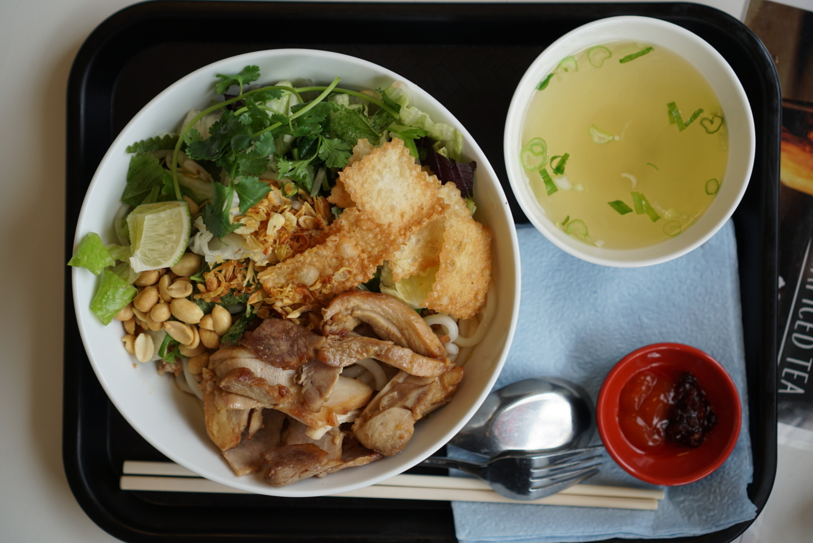 A dish of noodles, pork, chicken, and a mess of herbs, with a side of hot stock
