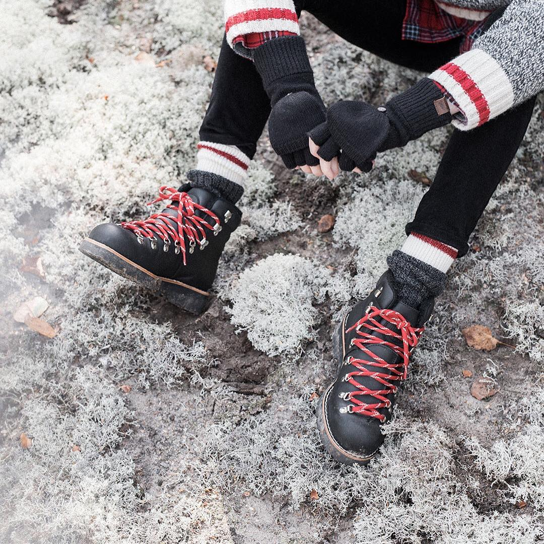 A woman sitting in the snow wearing snow boots and Roots Cabin Socks