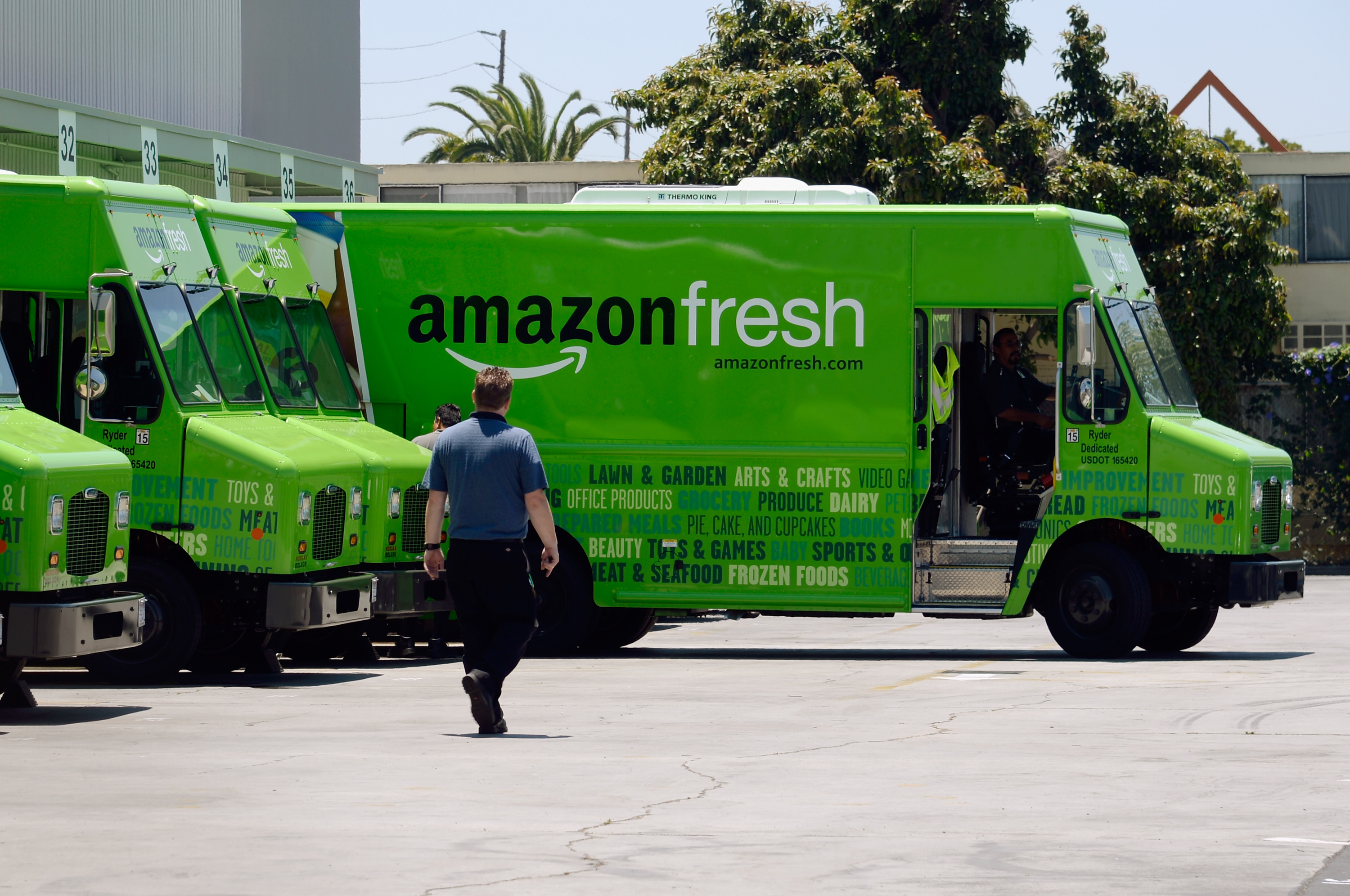 An Amazon Fresh delivery truck pulling out of a loading dock
