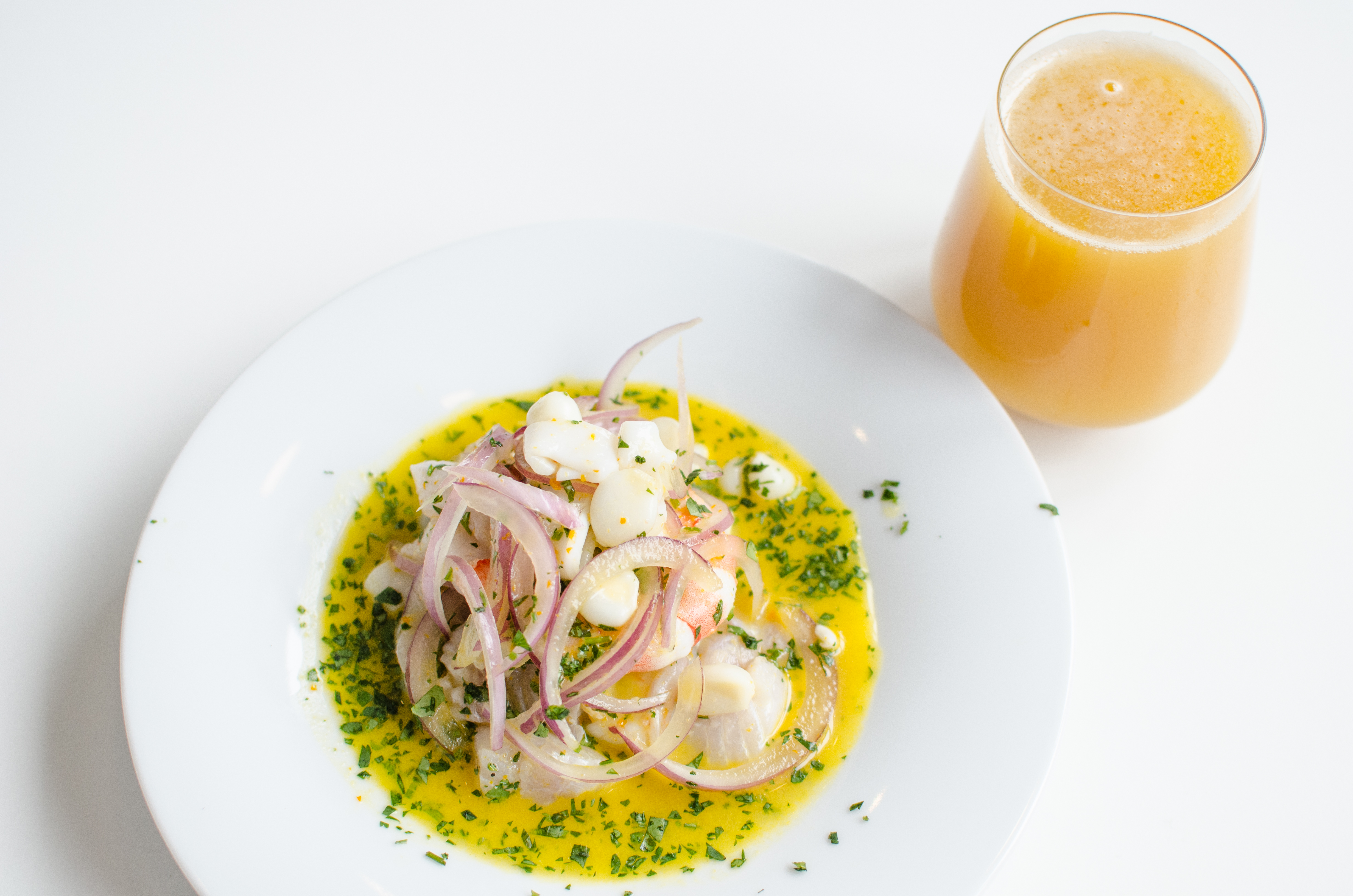 A vibrantly colored portion of ceviche is presented on a white plate on a white table, with a glass of beer on the side.