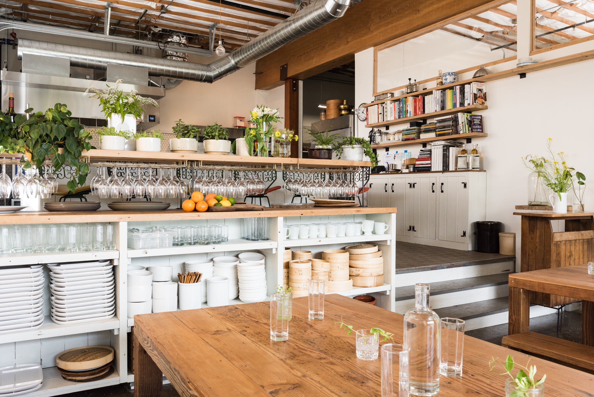 A communal table at Han Oak butts up against a set of built-in shelves next to a staircase, which leads into a small kitchen and chef's counter.
