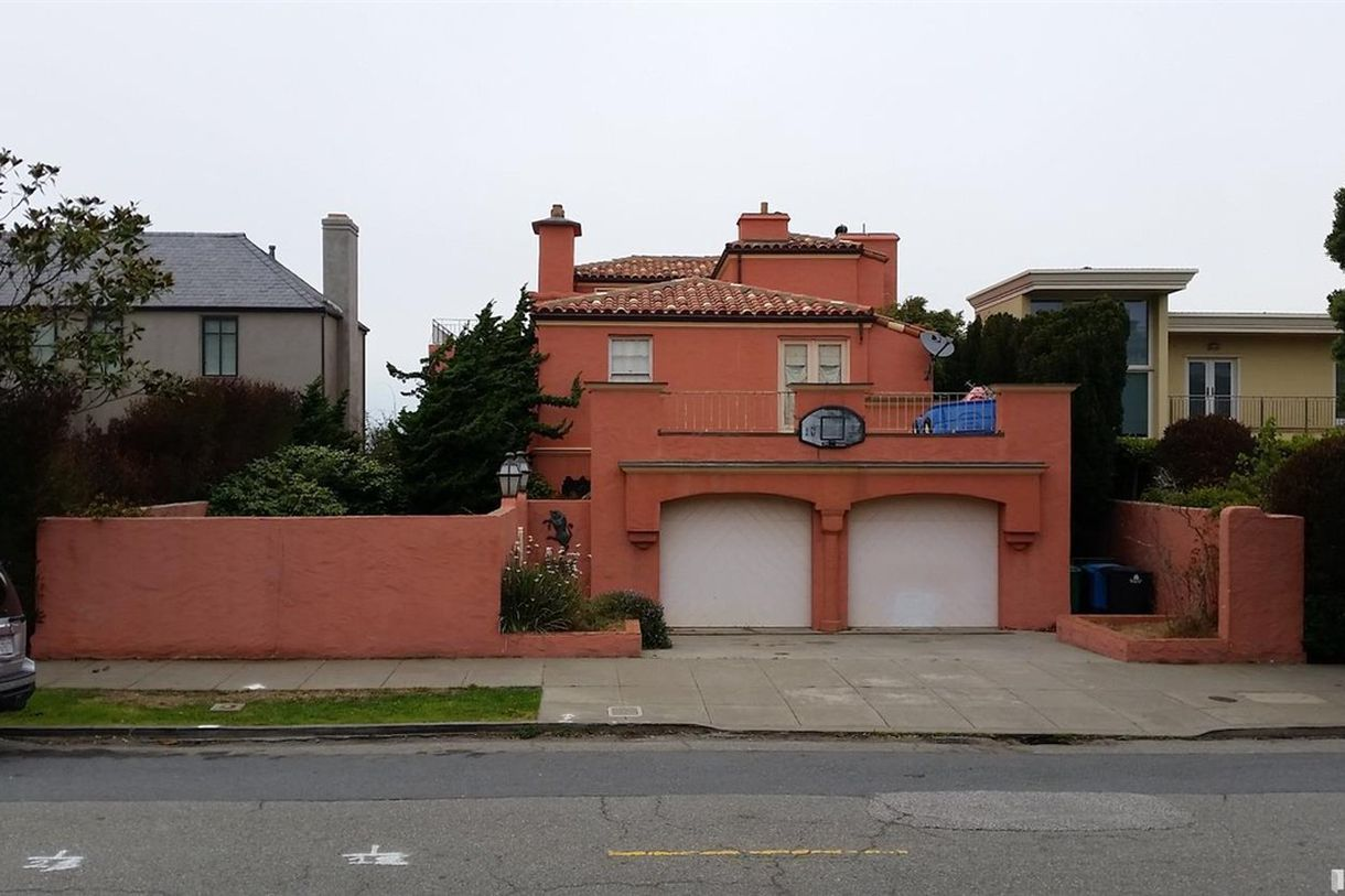 A red Mediterranean home with a stucco facade, a tile roof, and a dingy basketball hoop above the garage.
