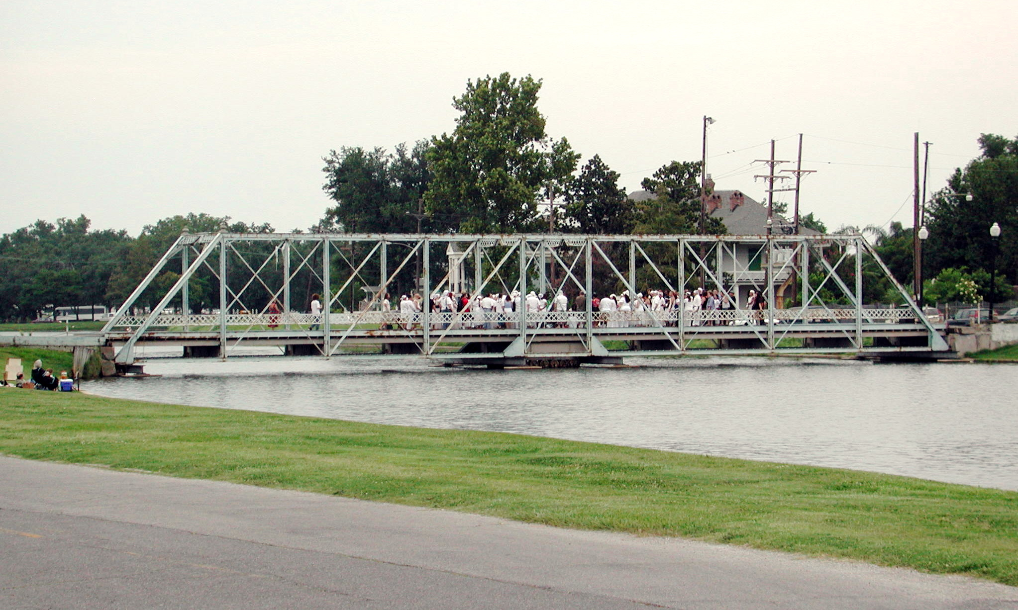 A pedestrian bridge spanning a small body of water. There are many people walking on the bridge.