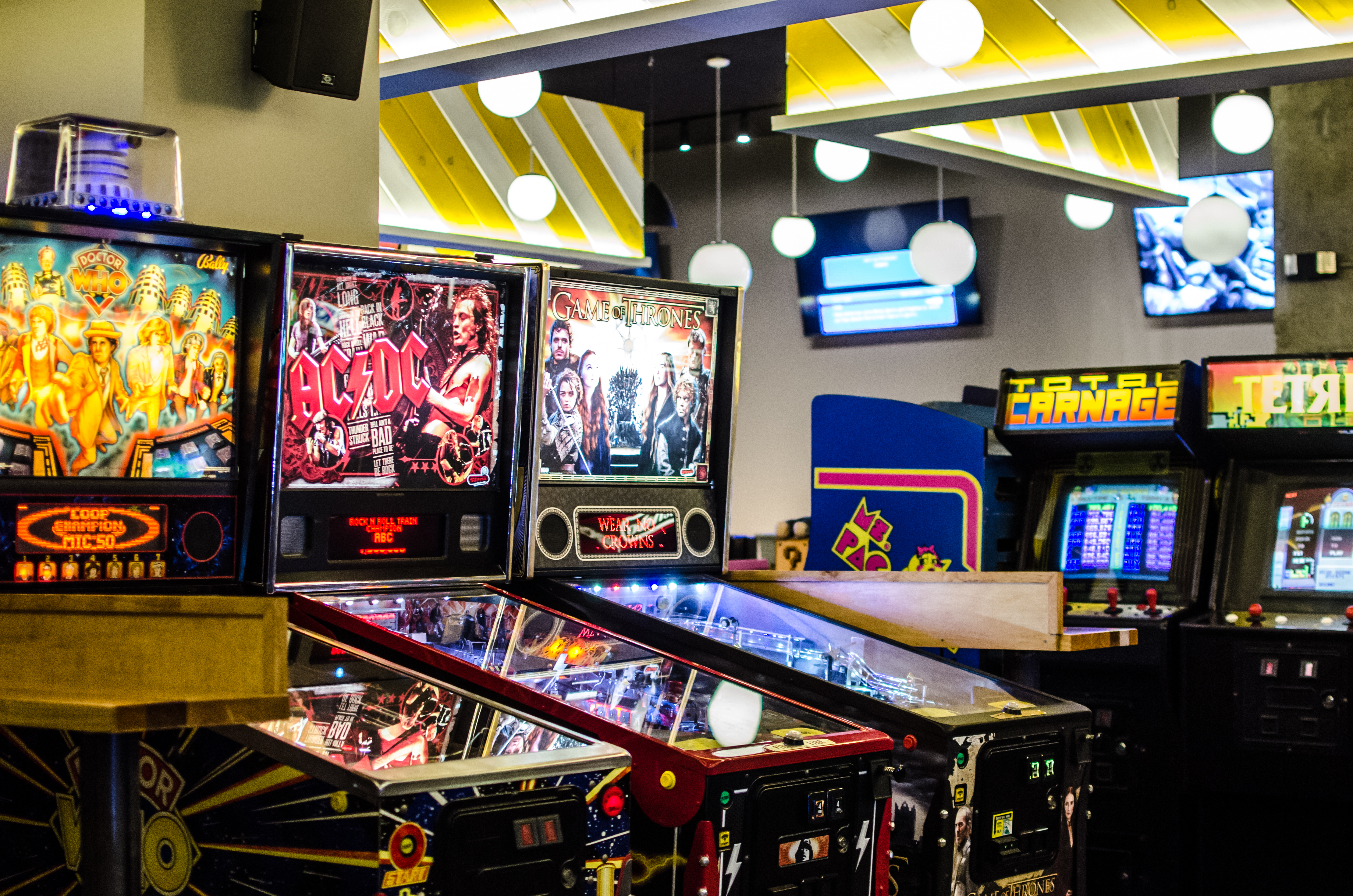 Arcade video games and pinball machines fill a room. White and yellow striped decorative panels hang from the ceiling.