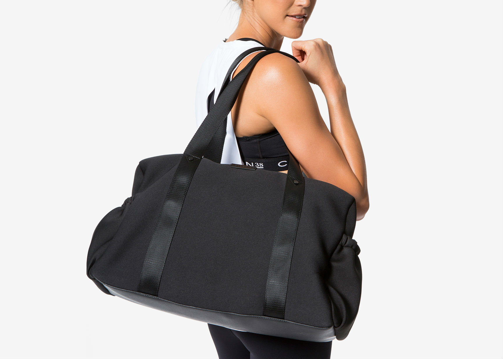 A model carrying a black gym bag
