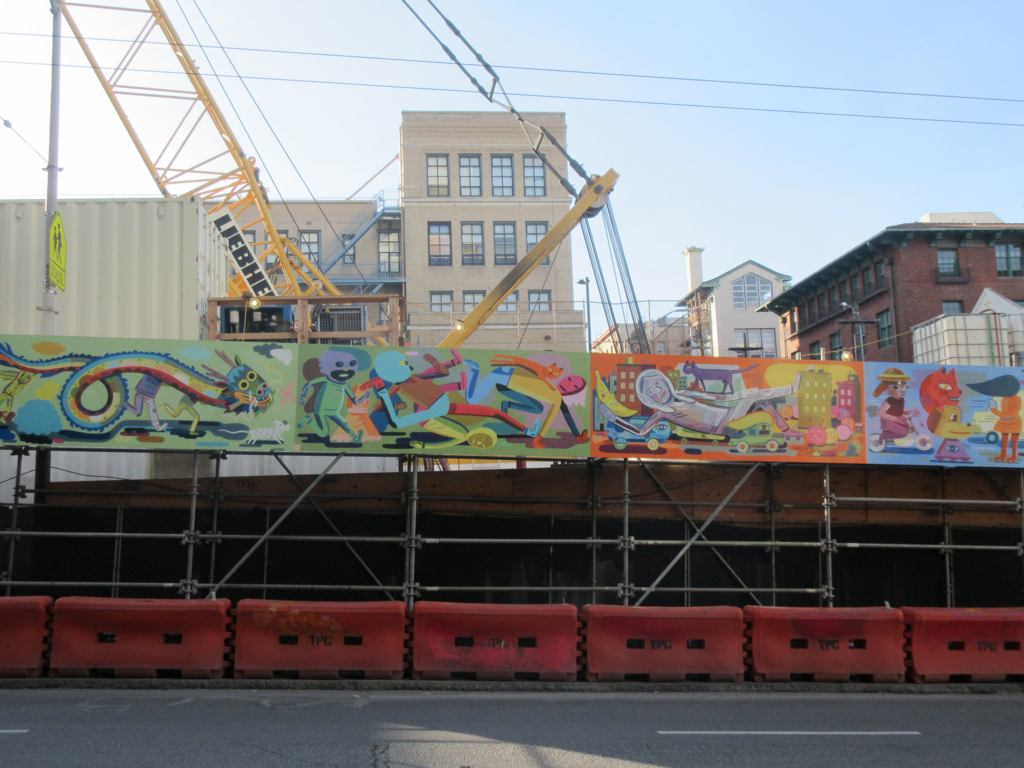A mural image of dozens of bizarre cartoon characters above a construction barricade on Stockton Street, with cranes and machinery behind it.