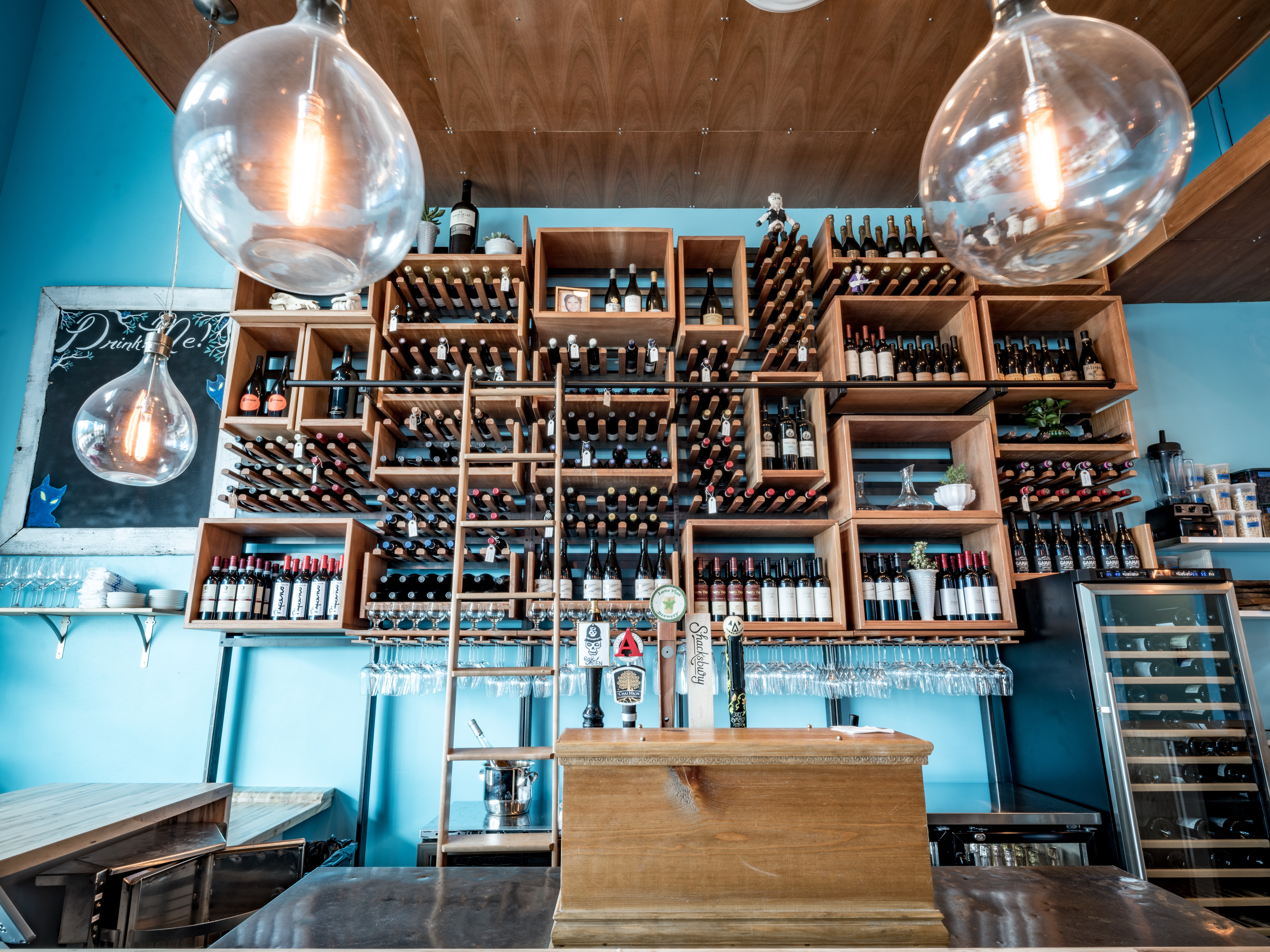 A big shelf of wine bottles with many compartments