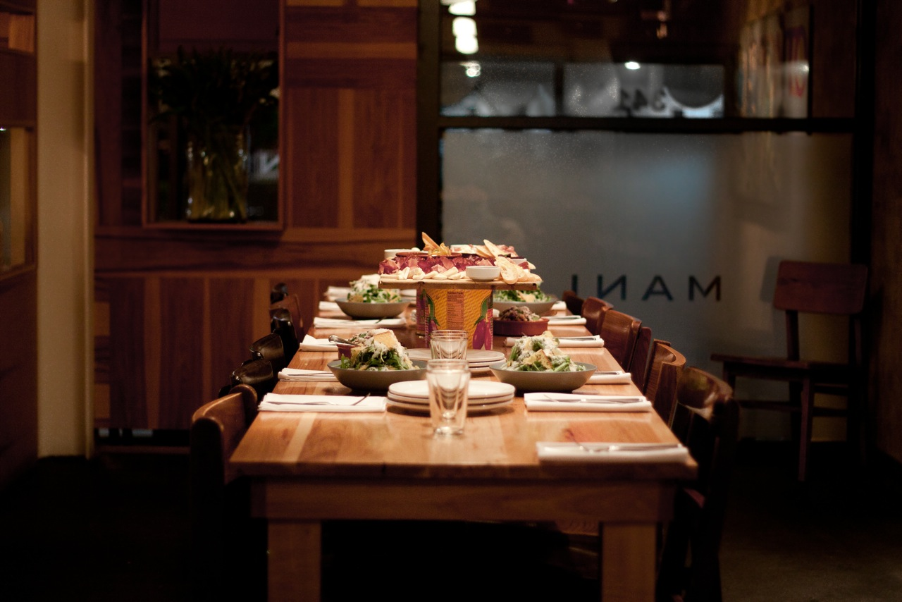 A dimly lit room with a large butcher block table set up with salads and a cheese plate on a pedestal.