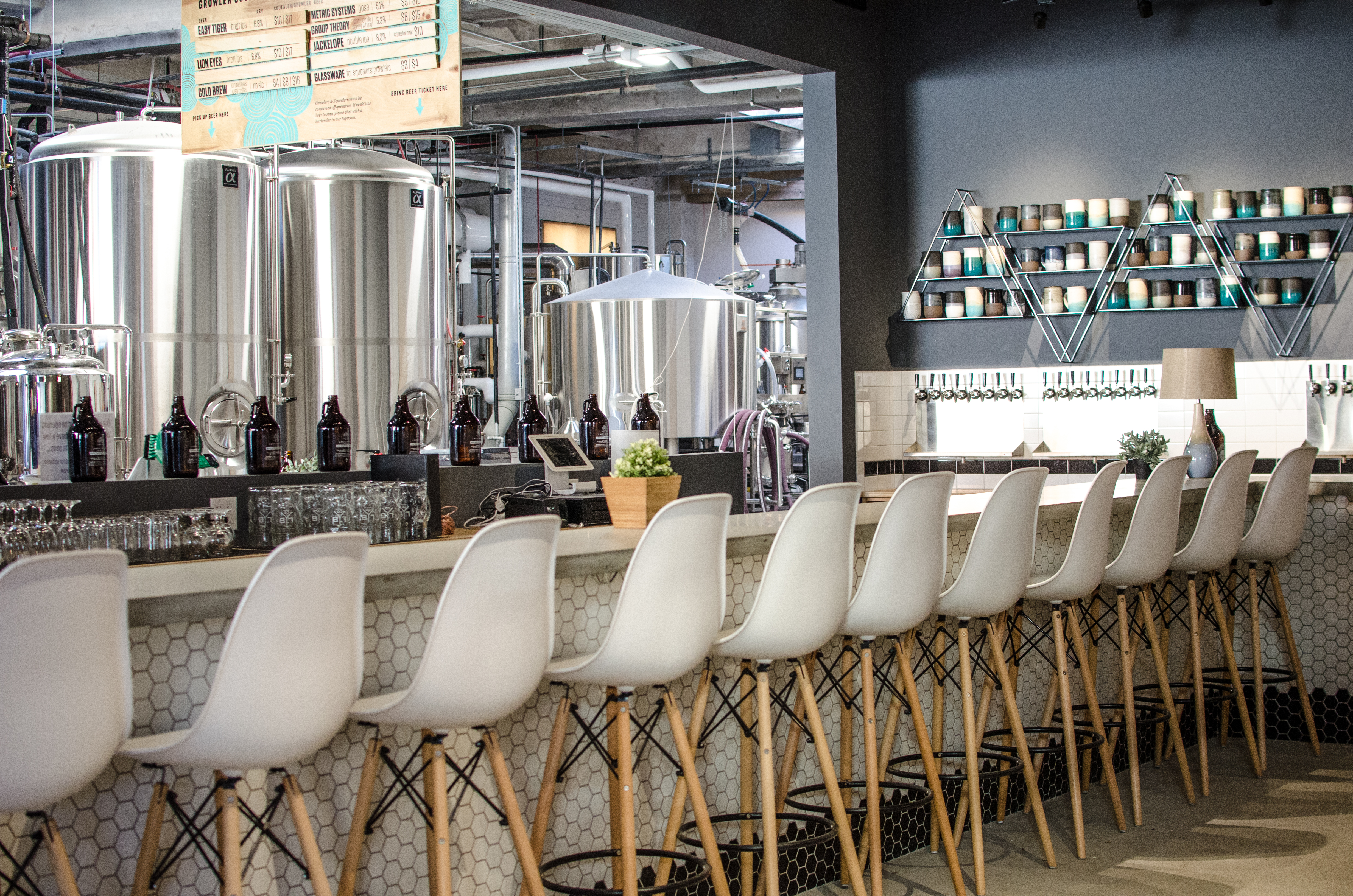 White bar stools line a concrete bar with white tiling that opens to brewing space with silver tanks
