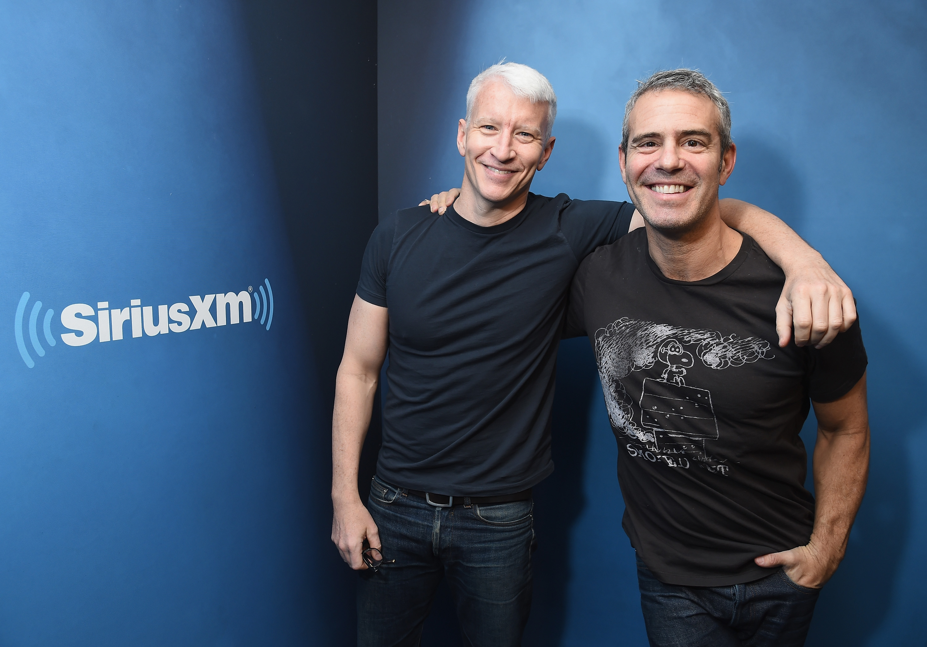TV journalist Anderson Cooper and host Andy Cohen pose next to a SiriusXM sign.
