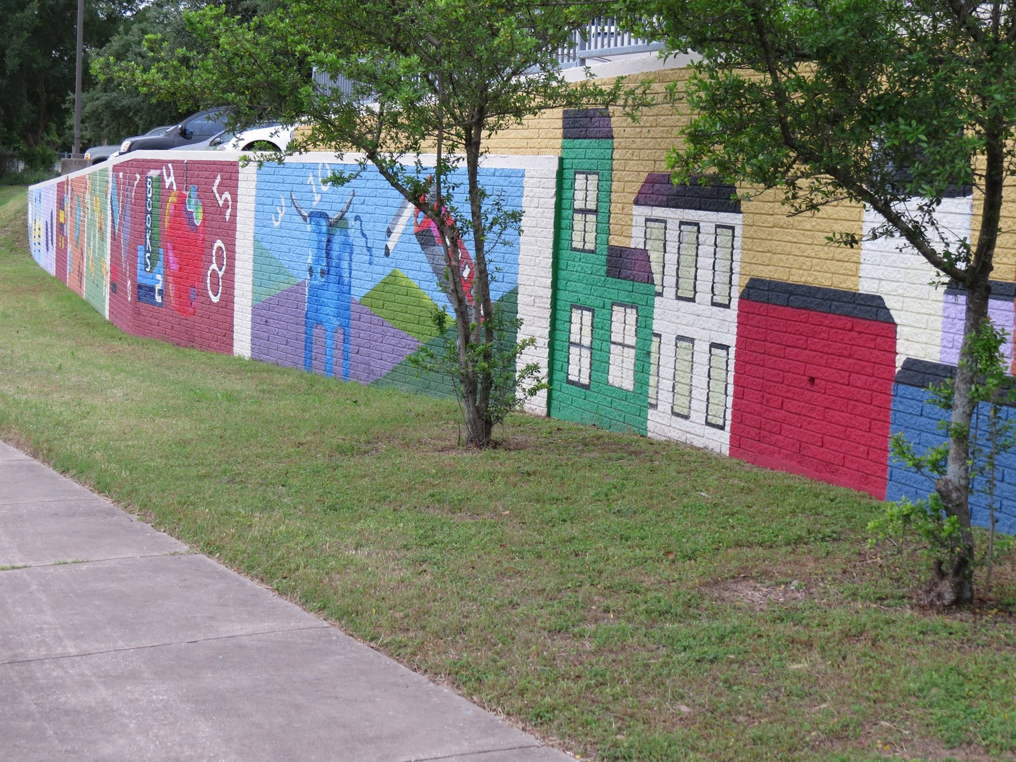 Parking lot retaining wall with painted panels depicting city and other scenes