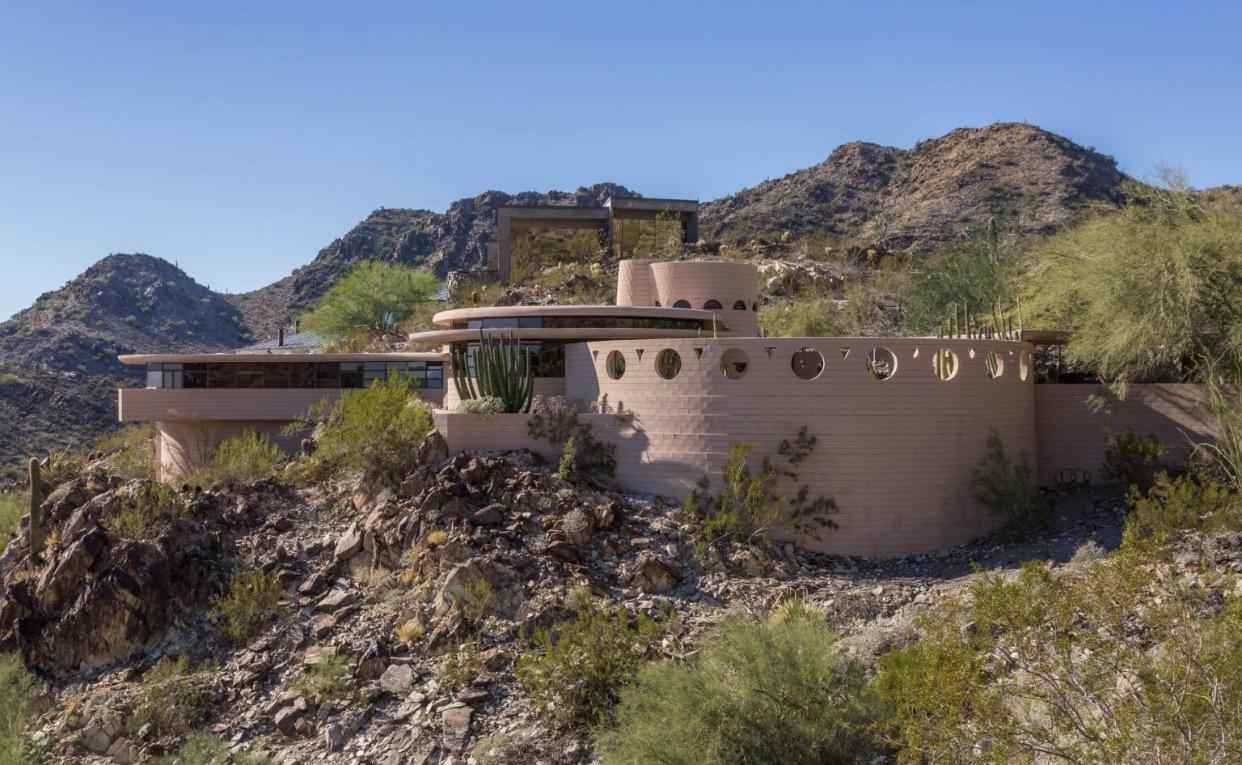 Circular tan-colored home nestled into mountains.