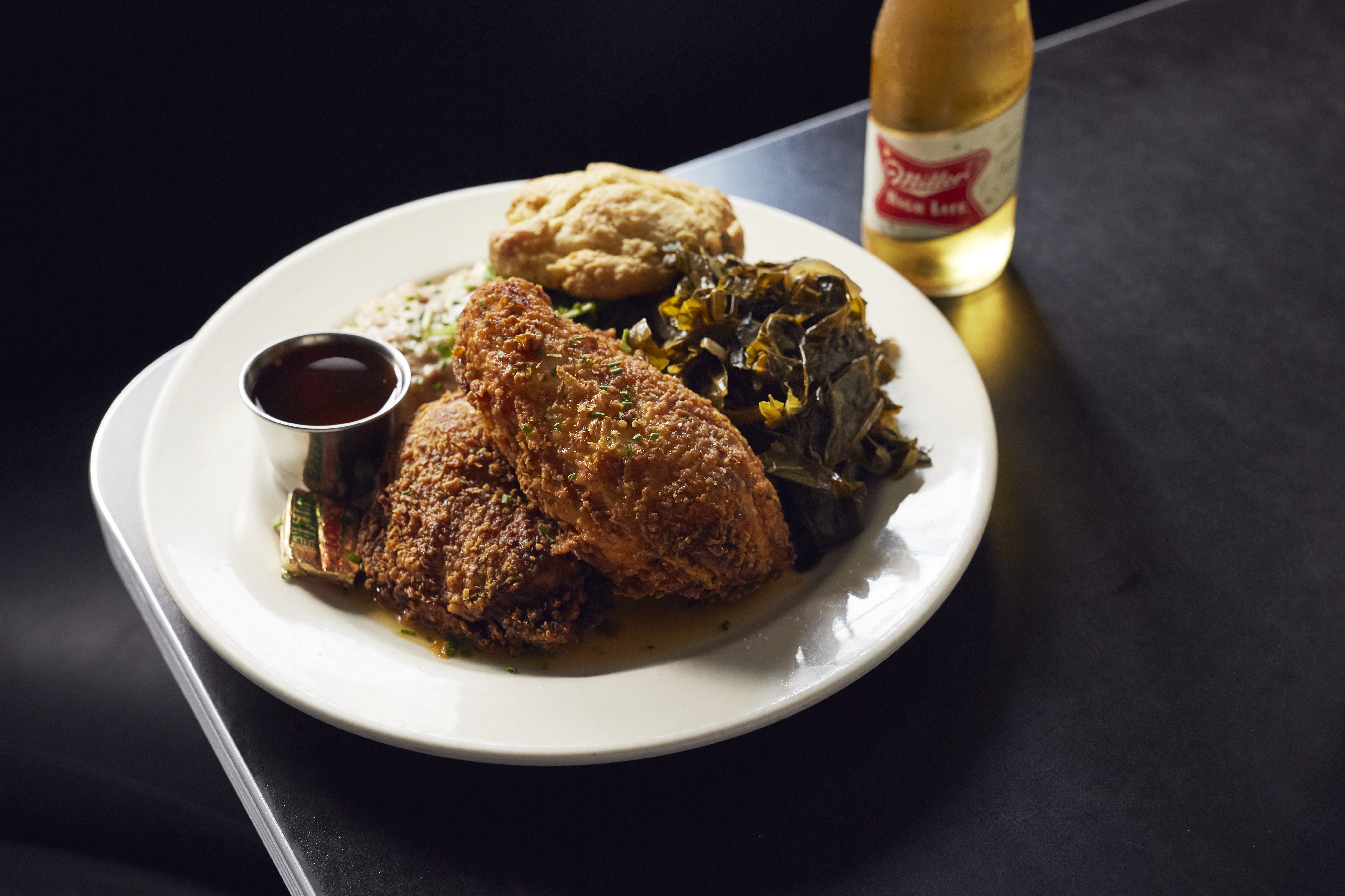 A plate of fried chicken with collard greens and a biscuit sits on a black tabletop on a black background. There's a bottle of Miller High Life to the side of the plate.