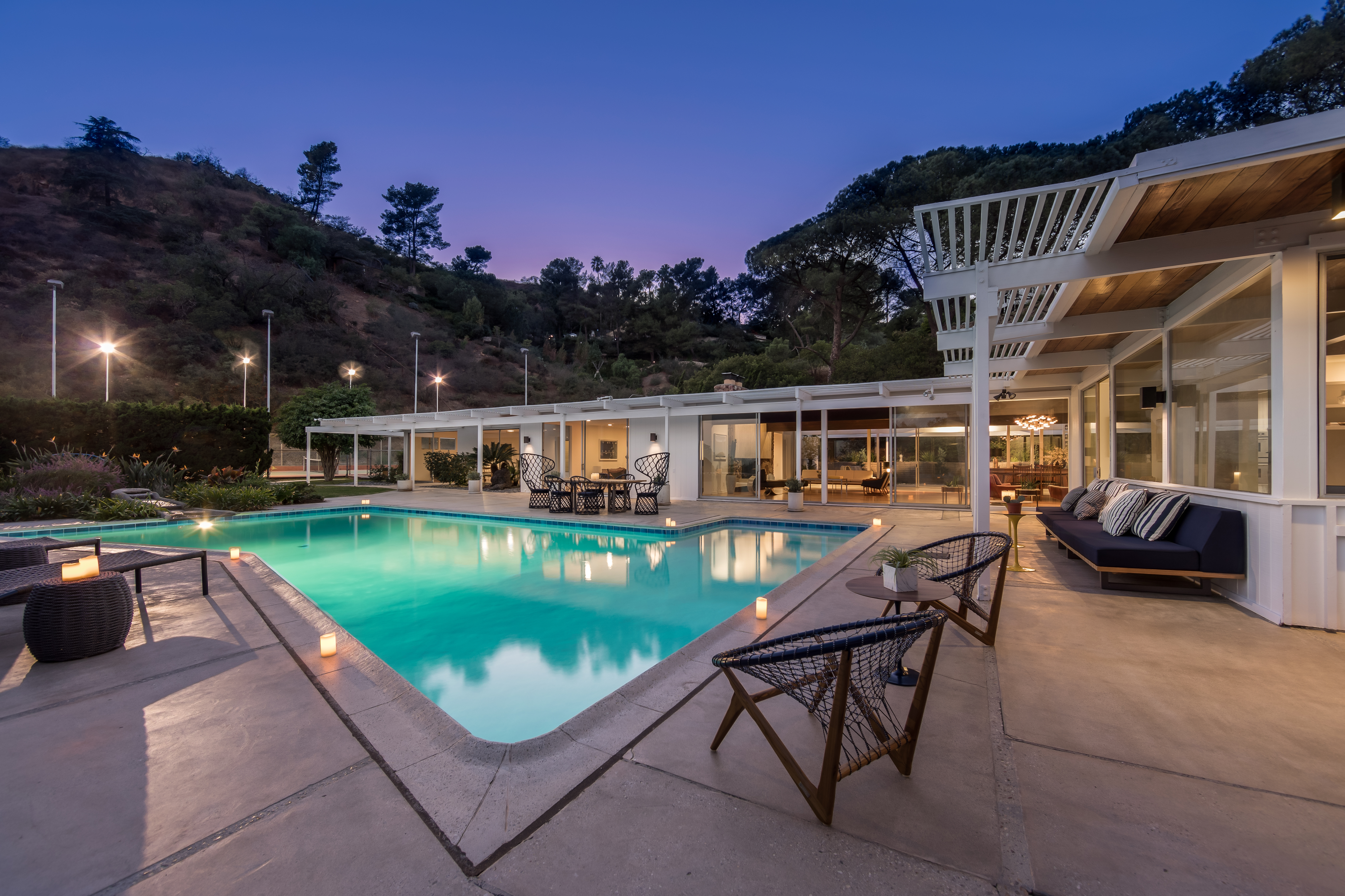 Night shot of backyard with pool and L-shaped flat-roofed home with glass walls surrounding it.