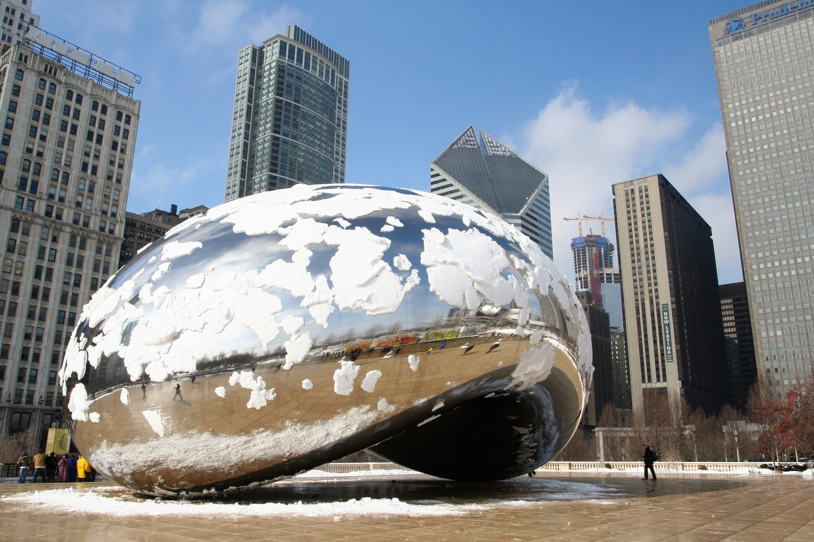 A silver sculpture covered in snow with tall buildings in the background.