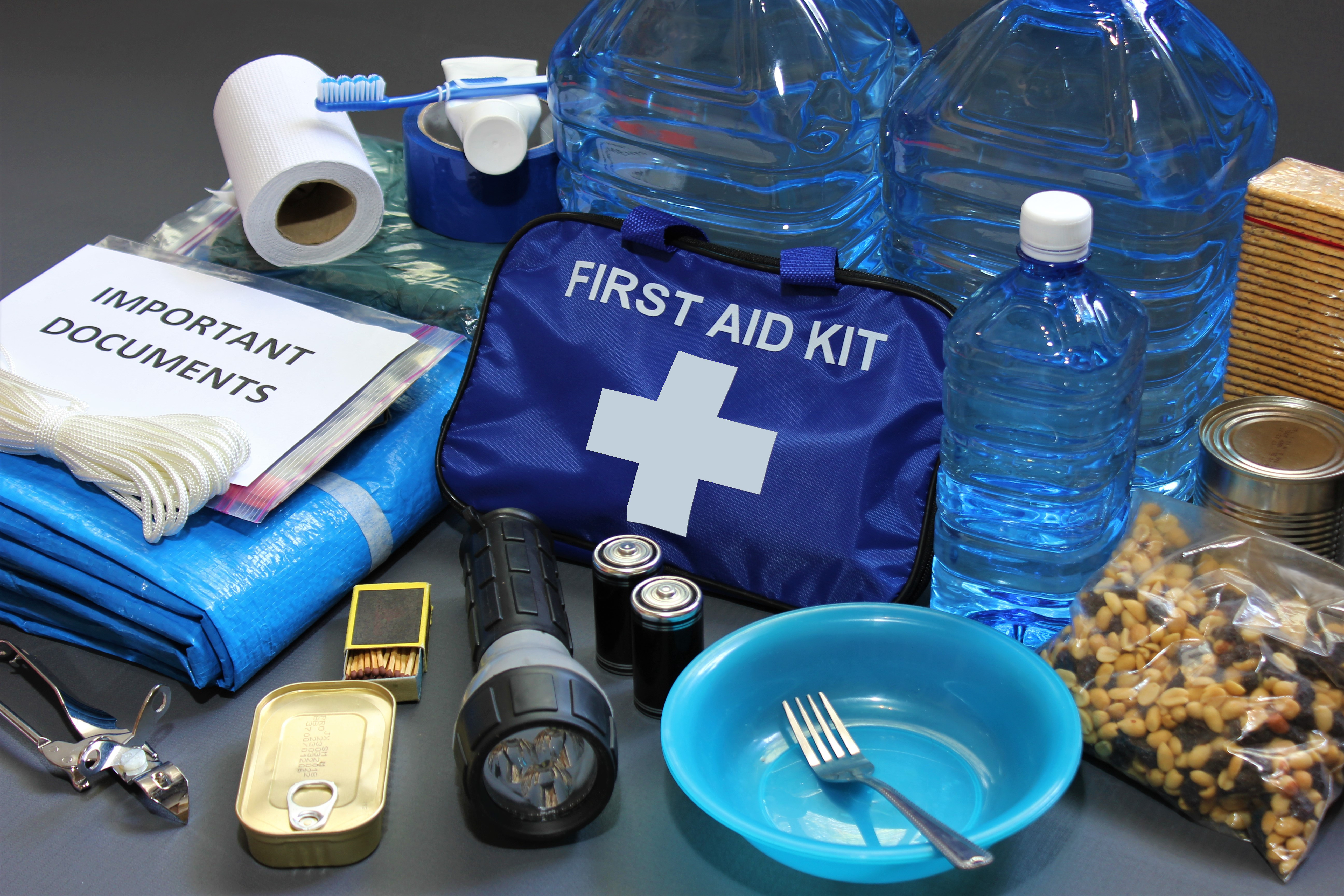 A first-aid kit with a bag, can opener, flashlight, toilet paper, bowl, fork, toothbrush.