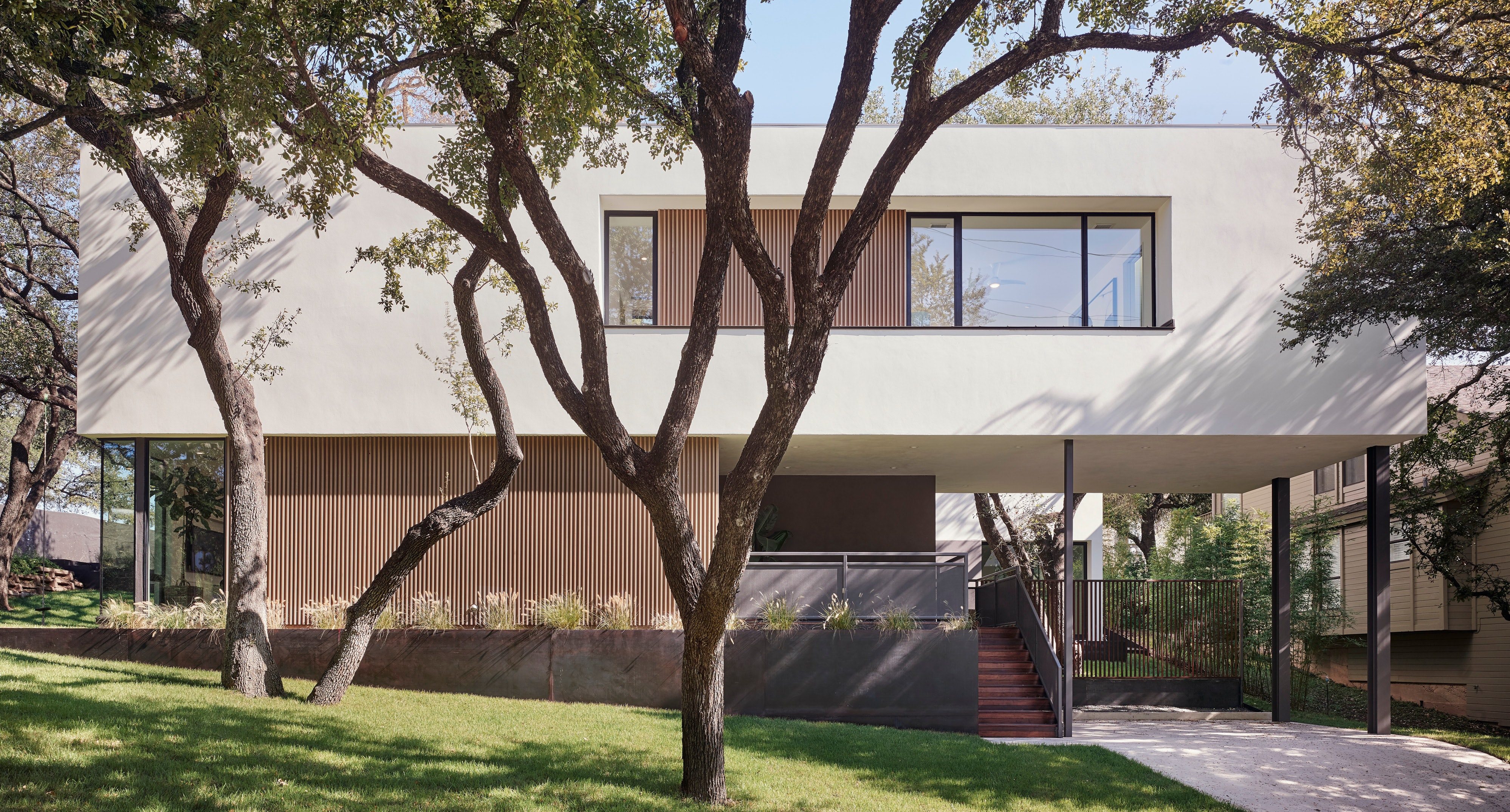 New contemporary with large horizontal white stucco second floor, smaller first story in glass and wood slatted screen