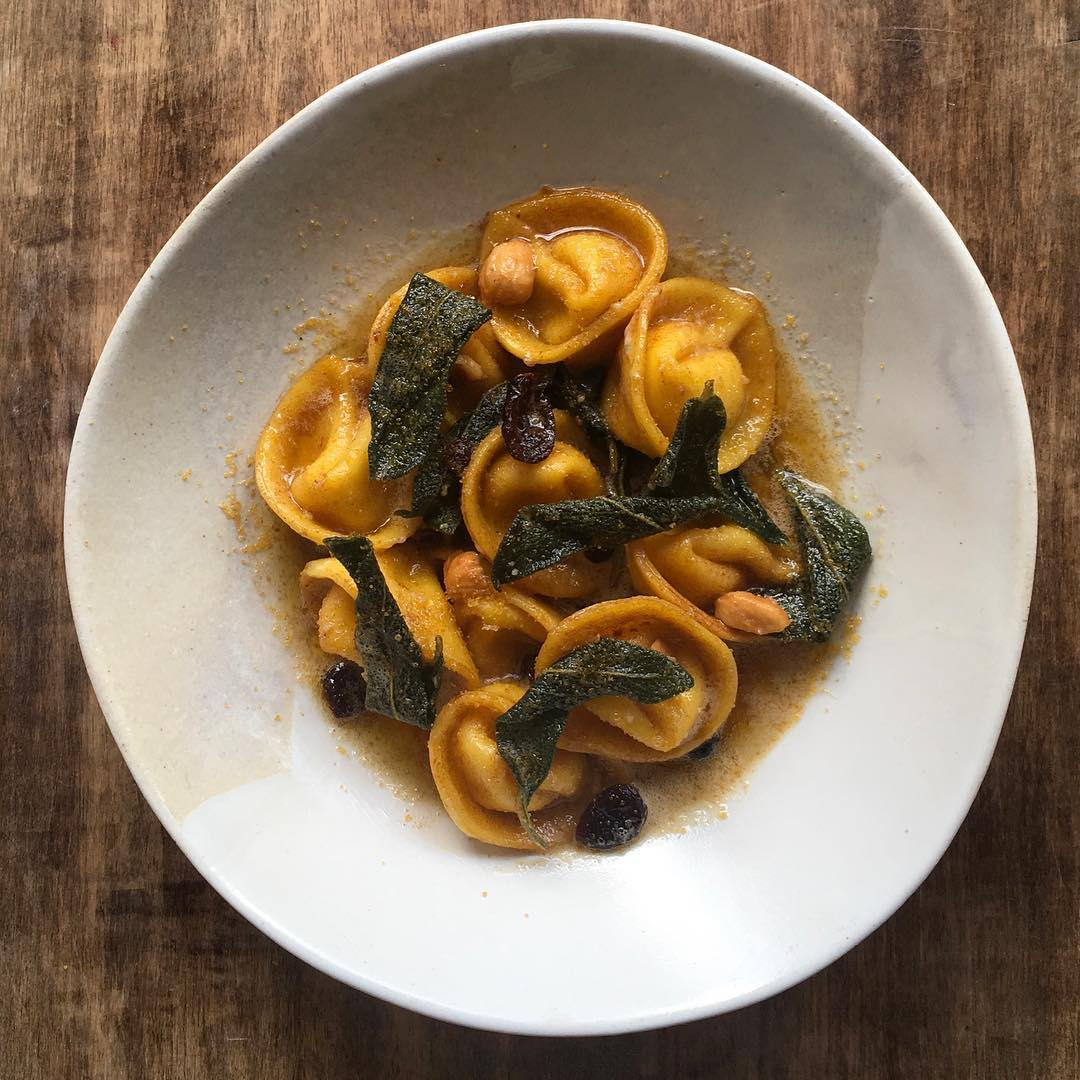 Sage tortellini at Wander restaurant, on a white plate on a wooden table