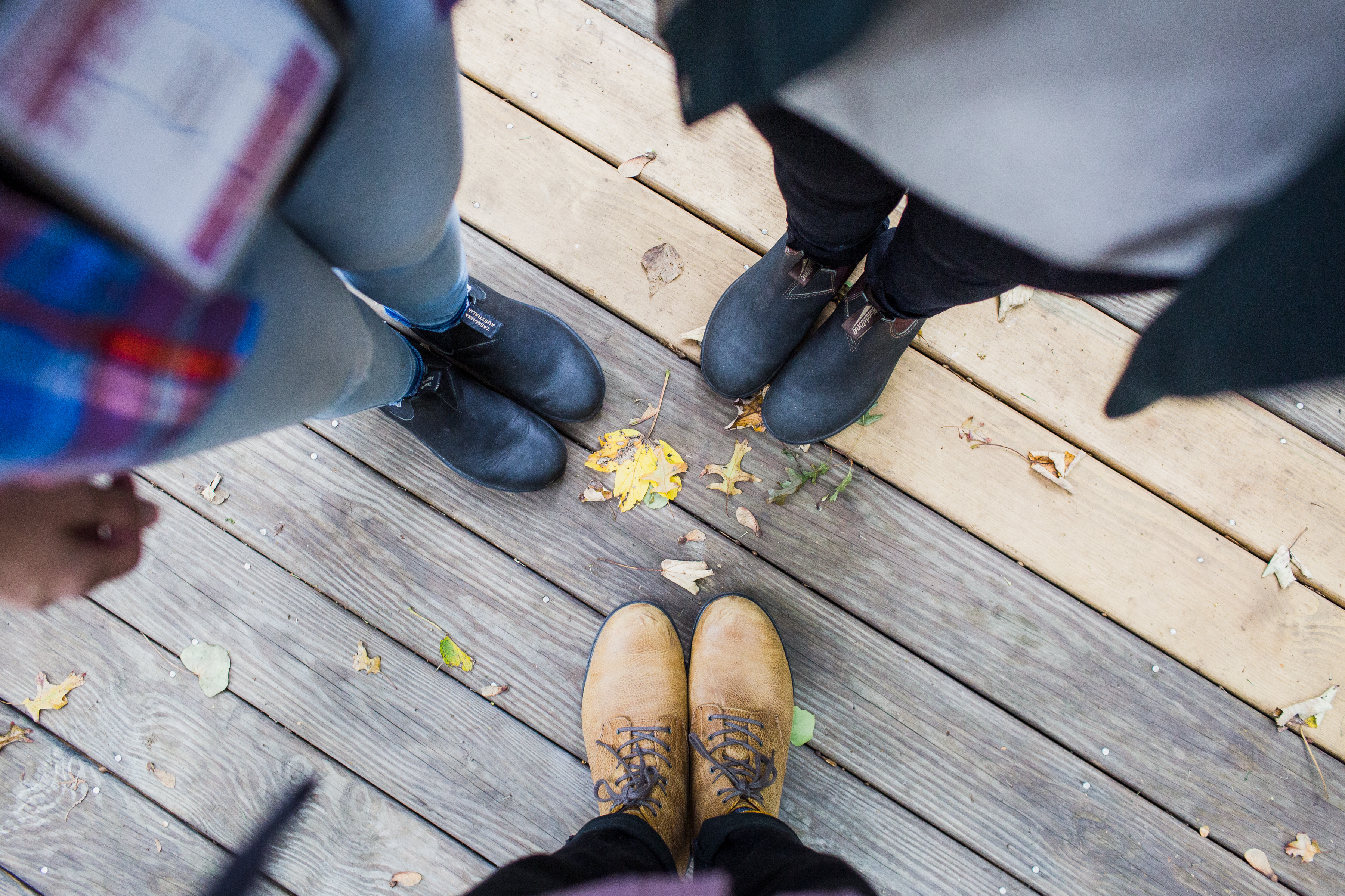 Three people looking down at their boots