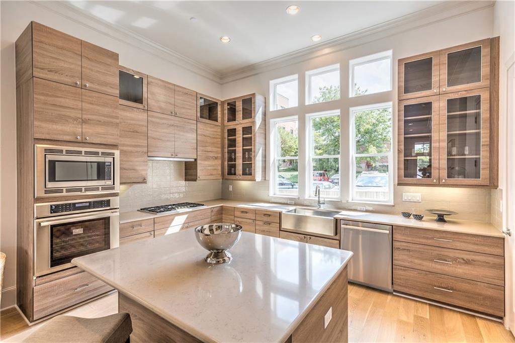 New kitchen with light-wood cabinets, island, big windows