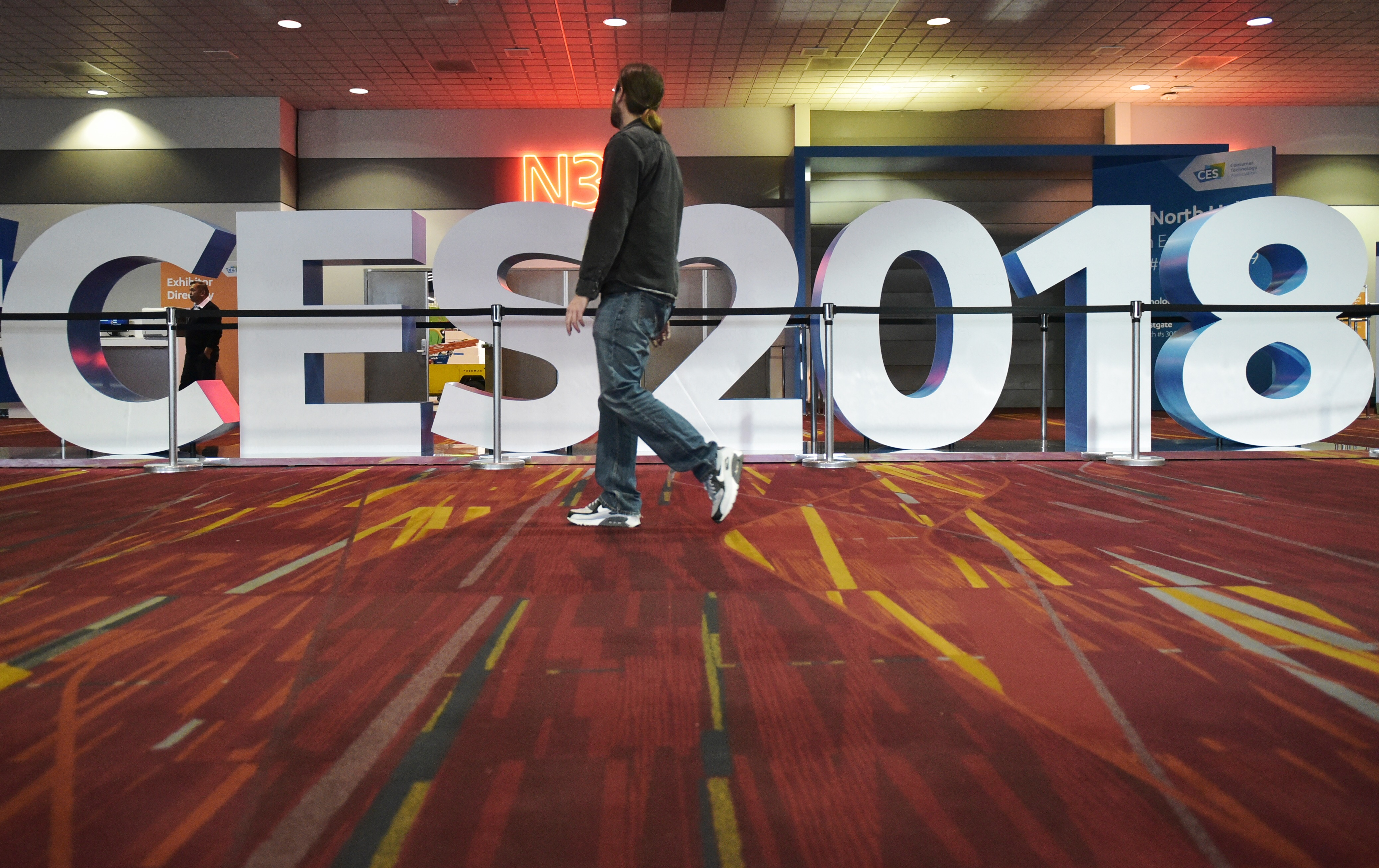 A conference attendee walks in front of the CES 2018 sign
