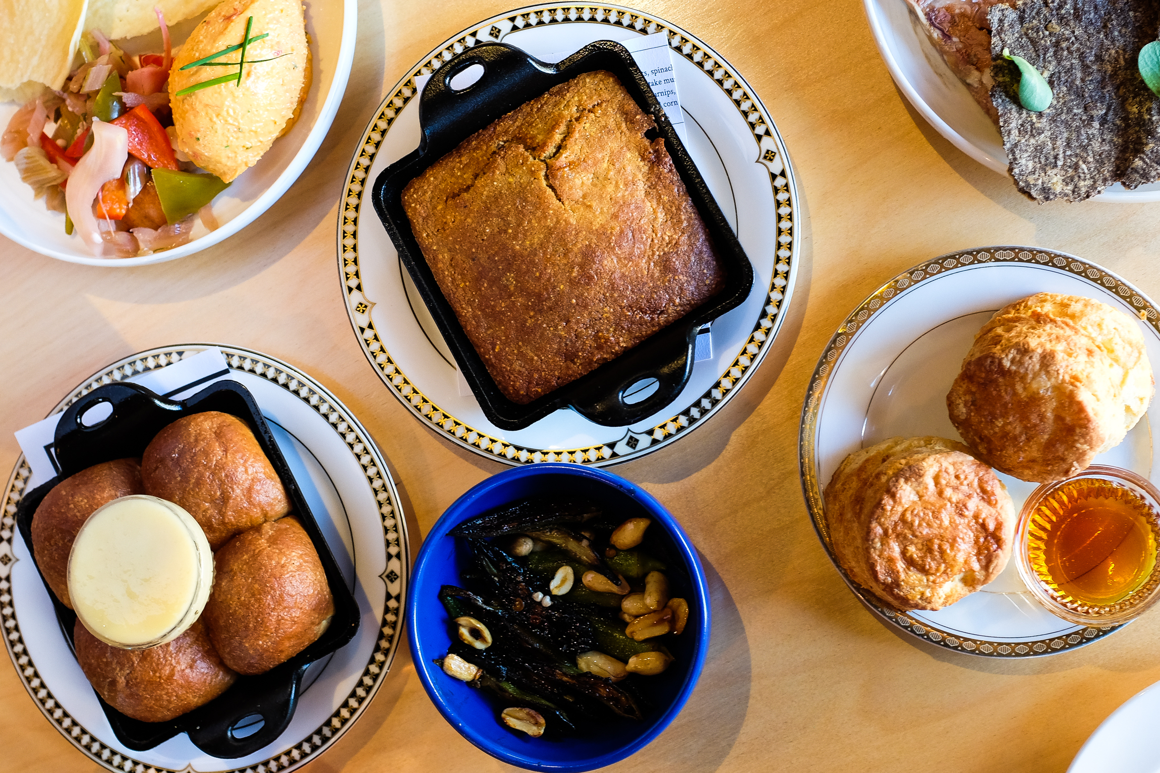 A spread of appetizers like cornbread and biscuits at revolutionary Southern restaurant Junebaby in Ravenna.