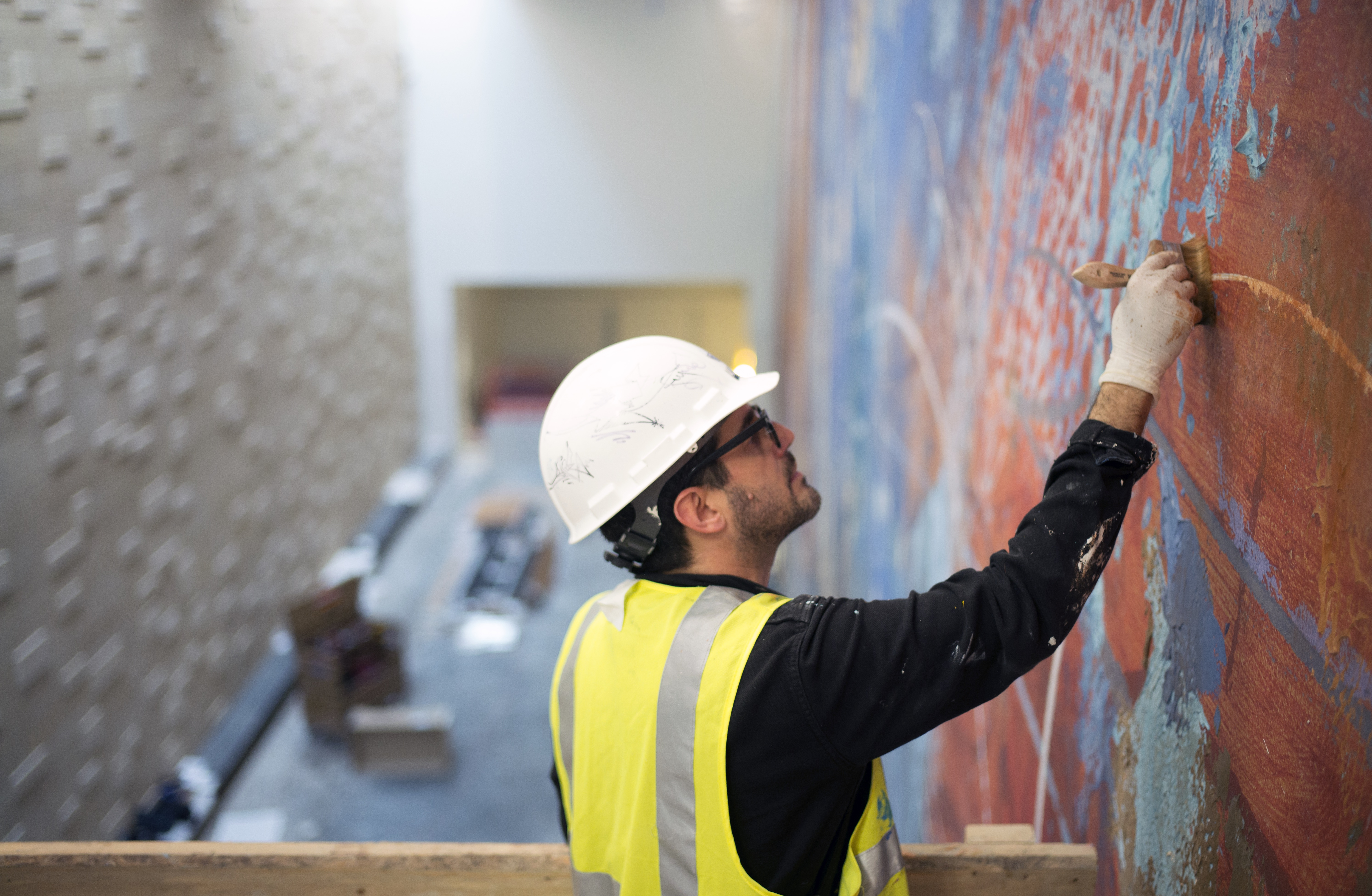A man in hardhat and yellow safety vest working on painting on scaffolding