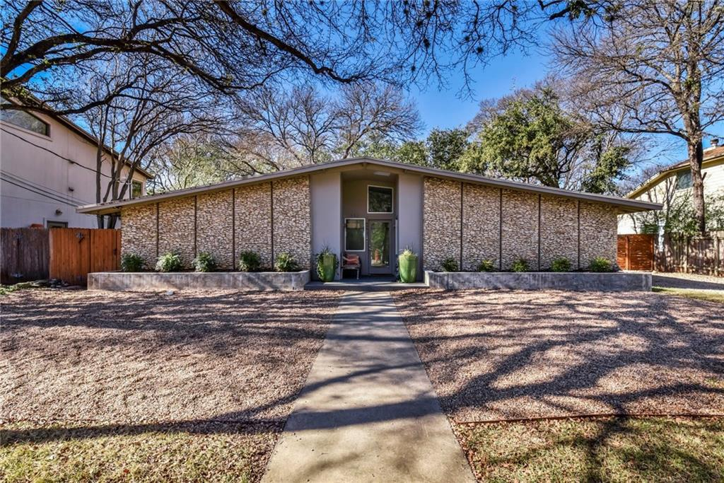 Stone midcentury house with symmetrical peaked roof