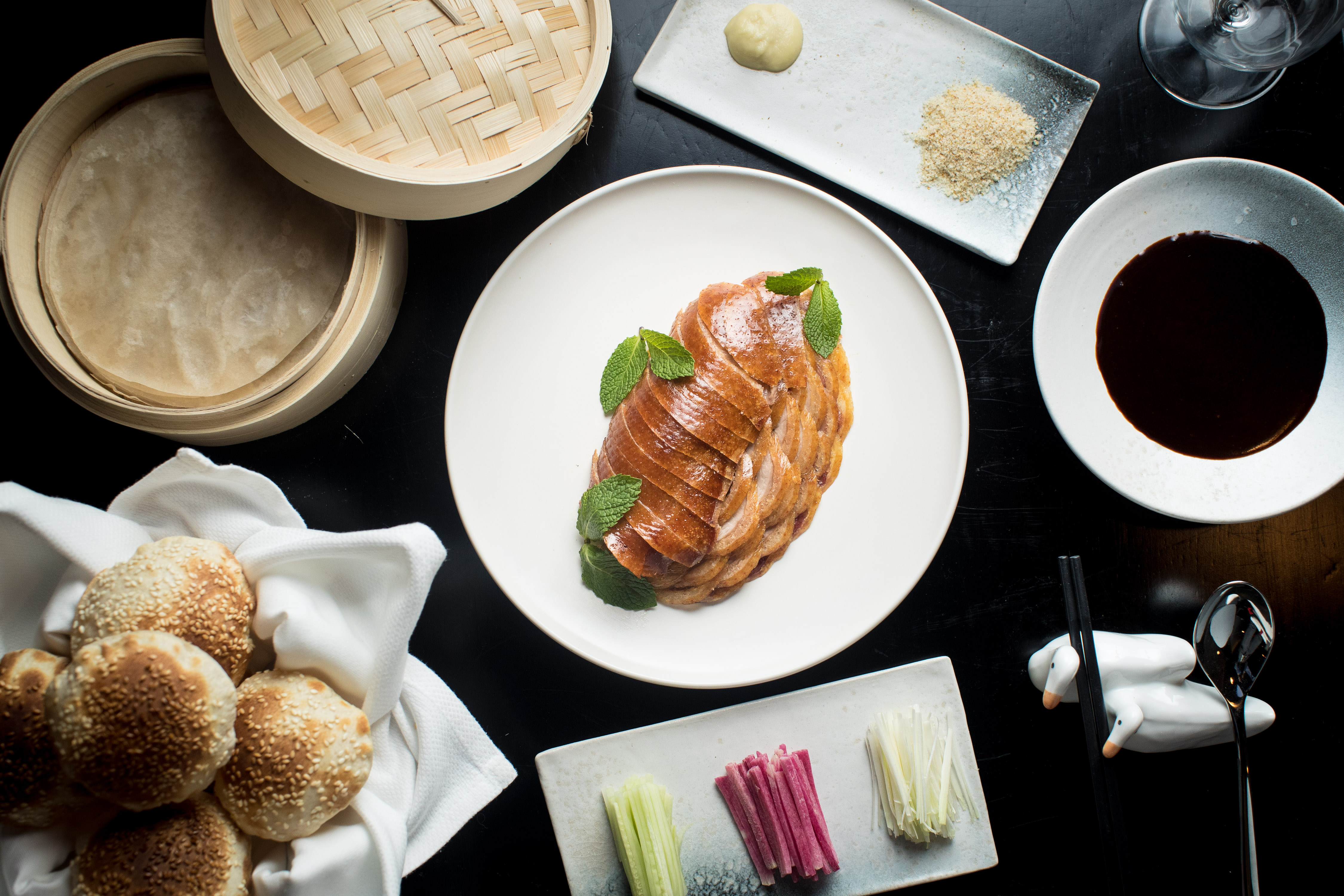 A spread of dishes laid out on a table demonstrating items on the restaurant's menu, including a centerpiece roast duck