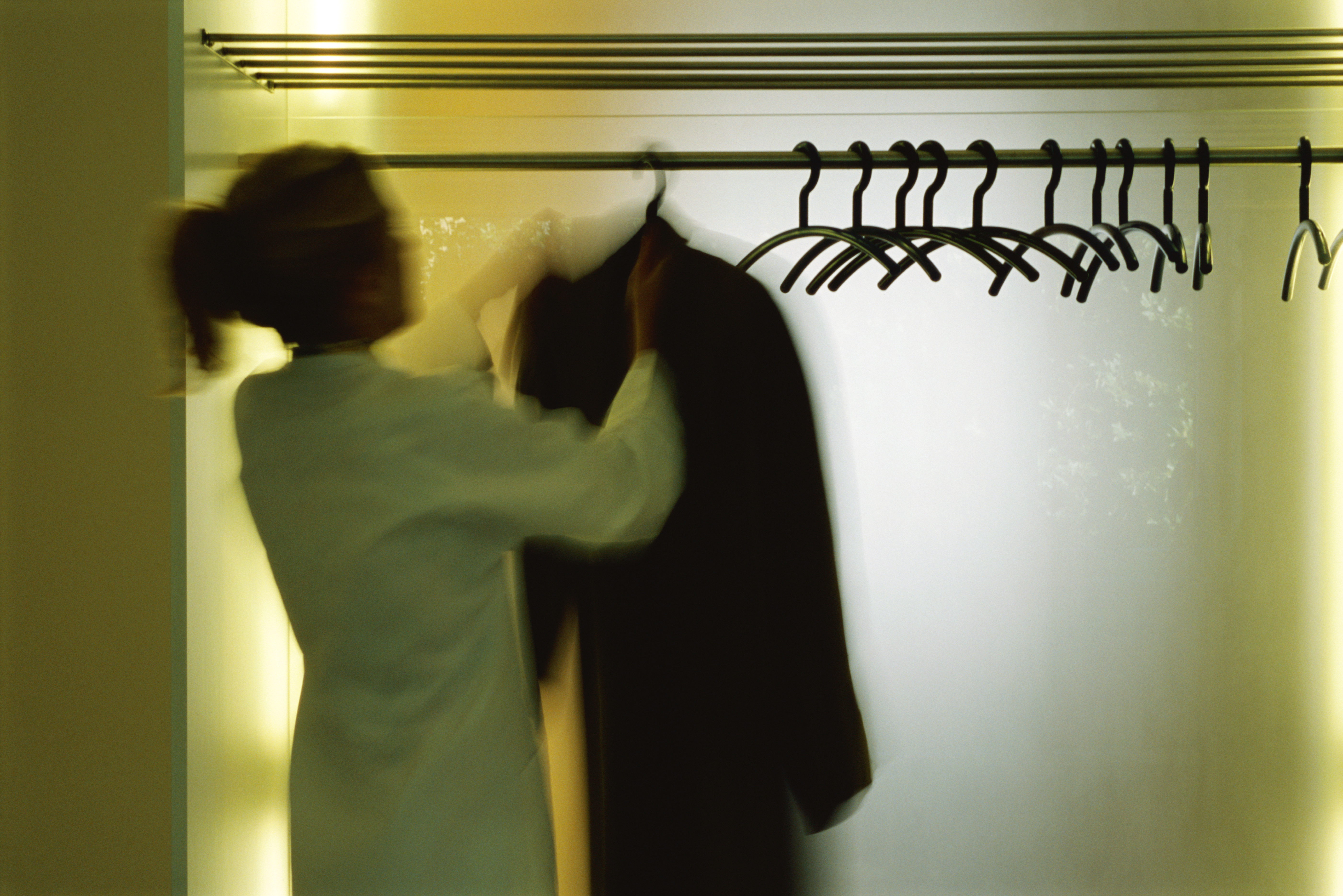 Woman hanging up coat in a closet