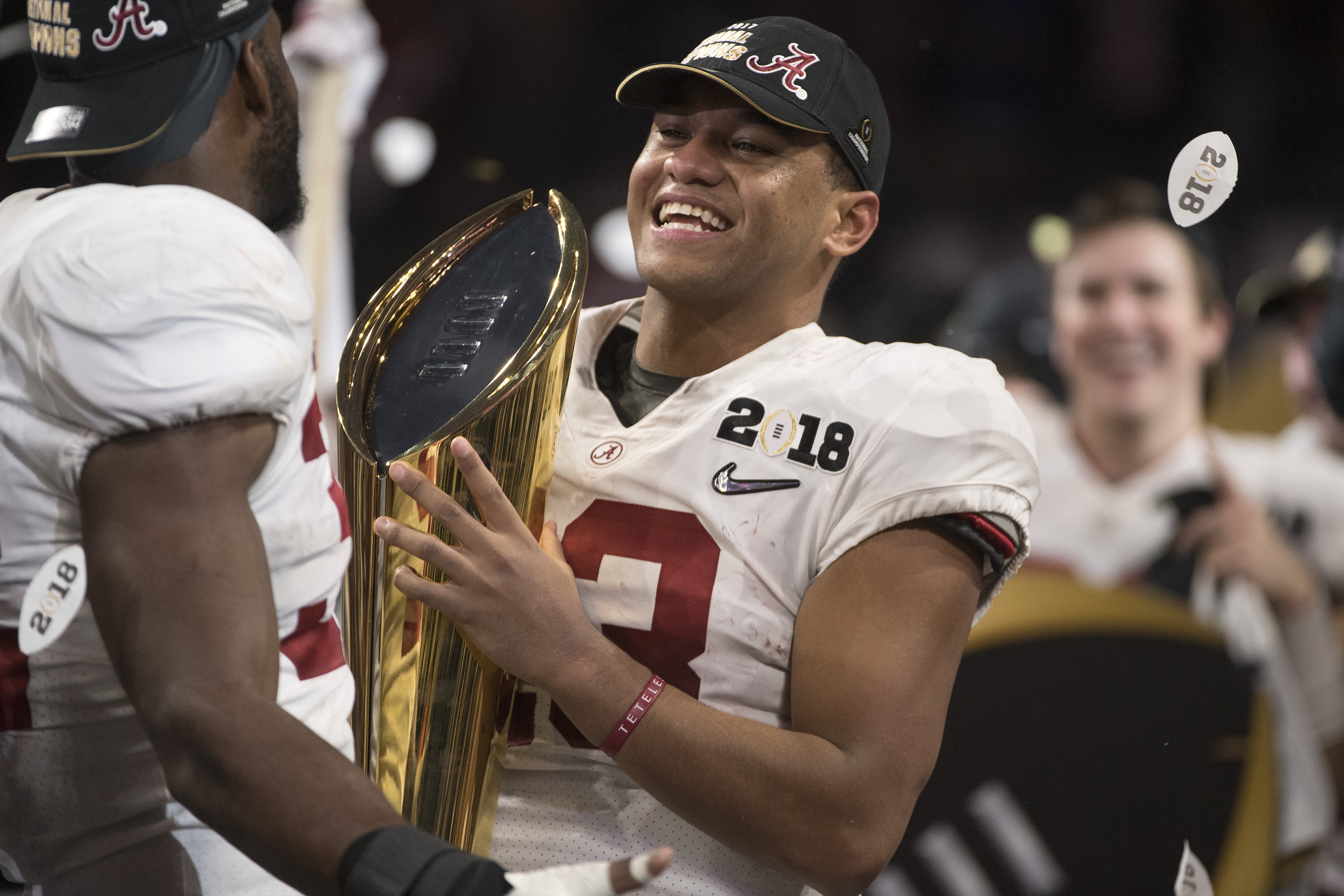 Tua Tagovailoa smiling and holding the national championship trophy