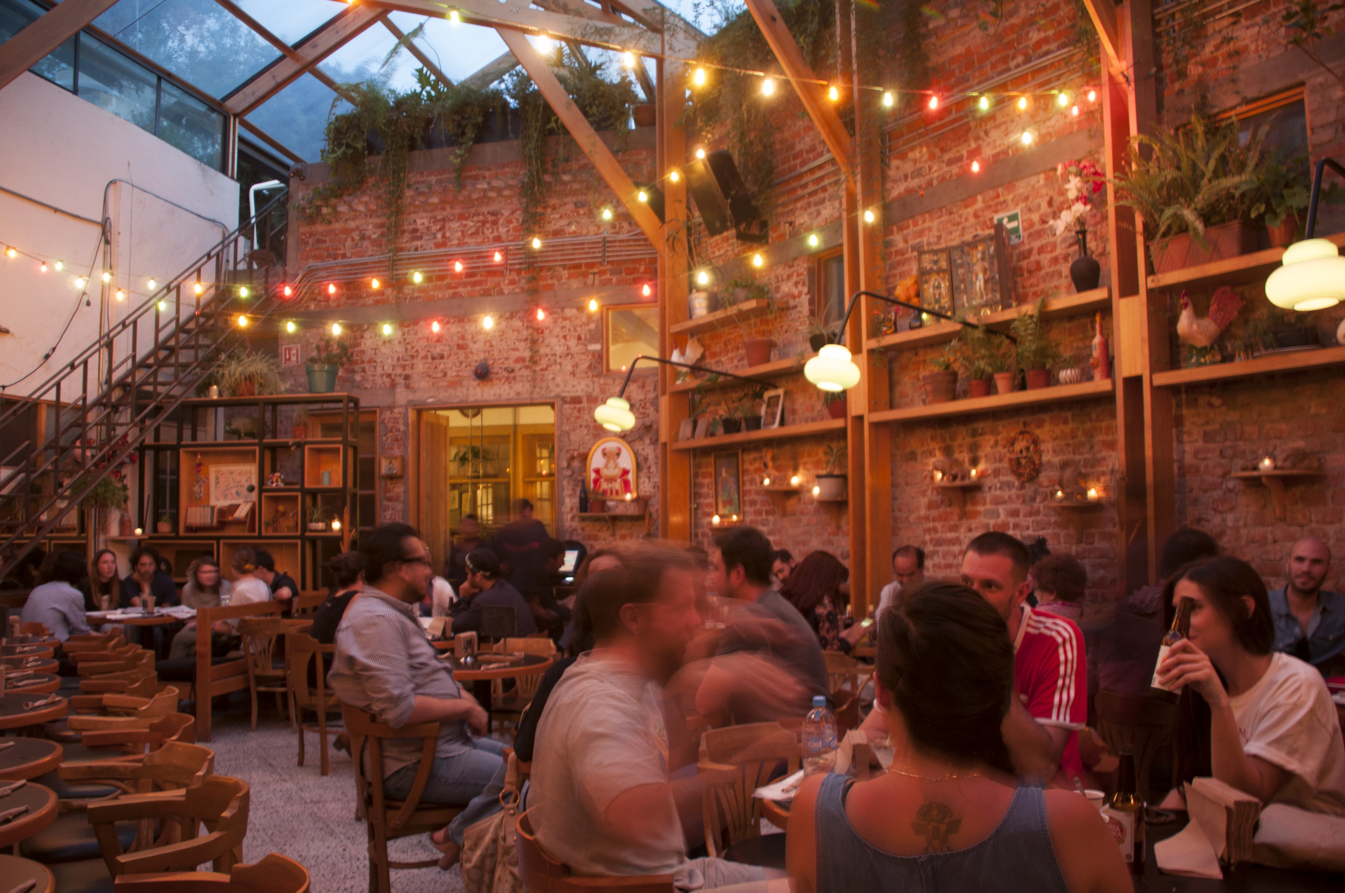 A restaurant interior, with tables full of diners, double height exposed brick walls covered with decorations, and a glass roof