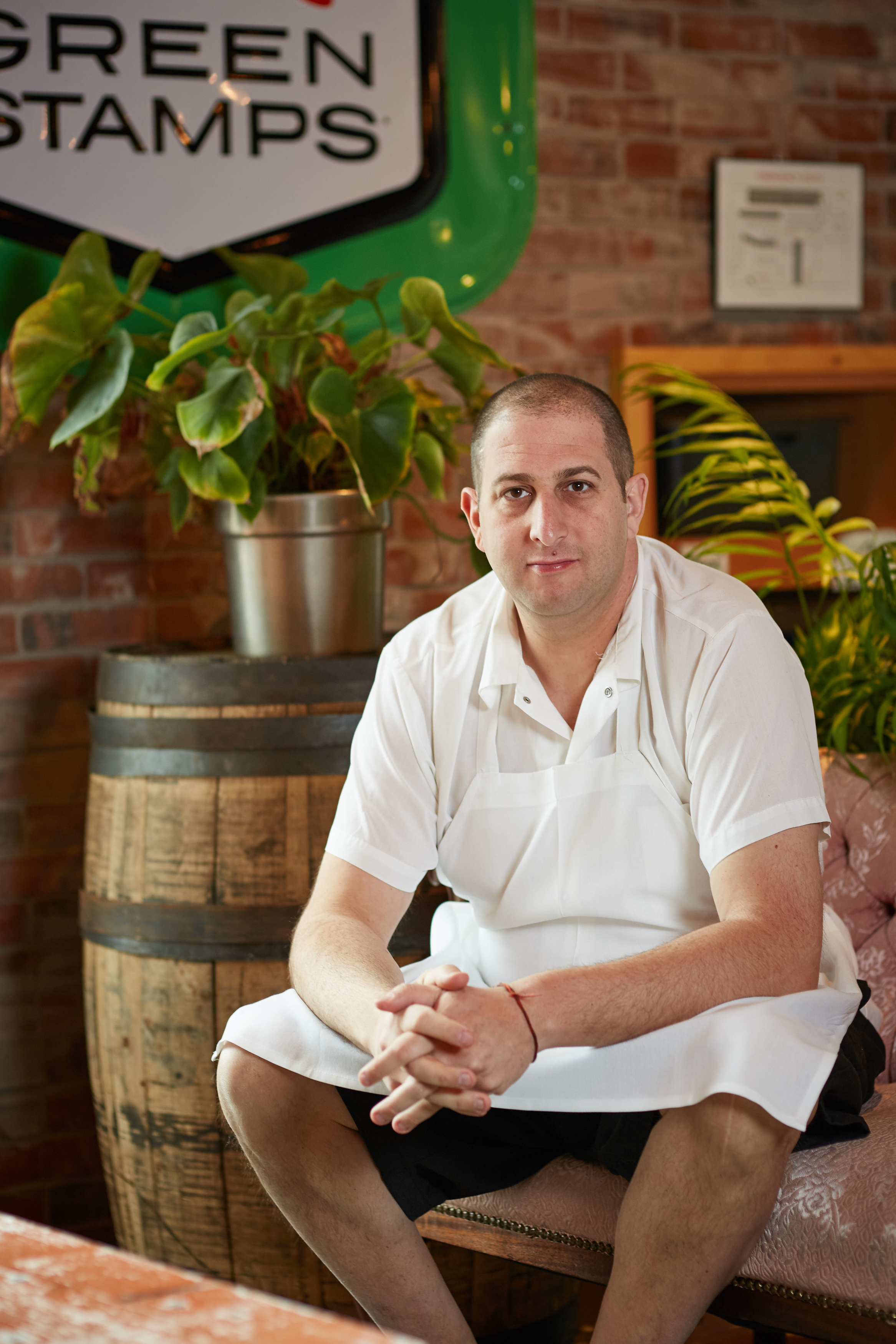 """A photo of chef Steve """"Nookie"""" Postal, wearing chef's whites and sitting in front of a barrel and greenery in a restaurant"""