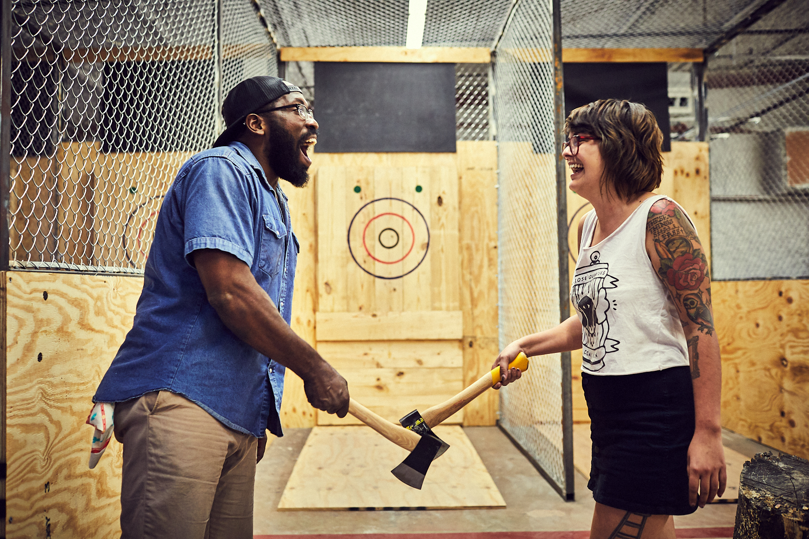 Two participants at an Urban Axes location smile and touch axes —the ax-throwing equivalent of a handshake — before beginning a round
