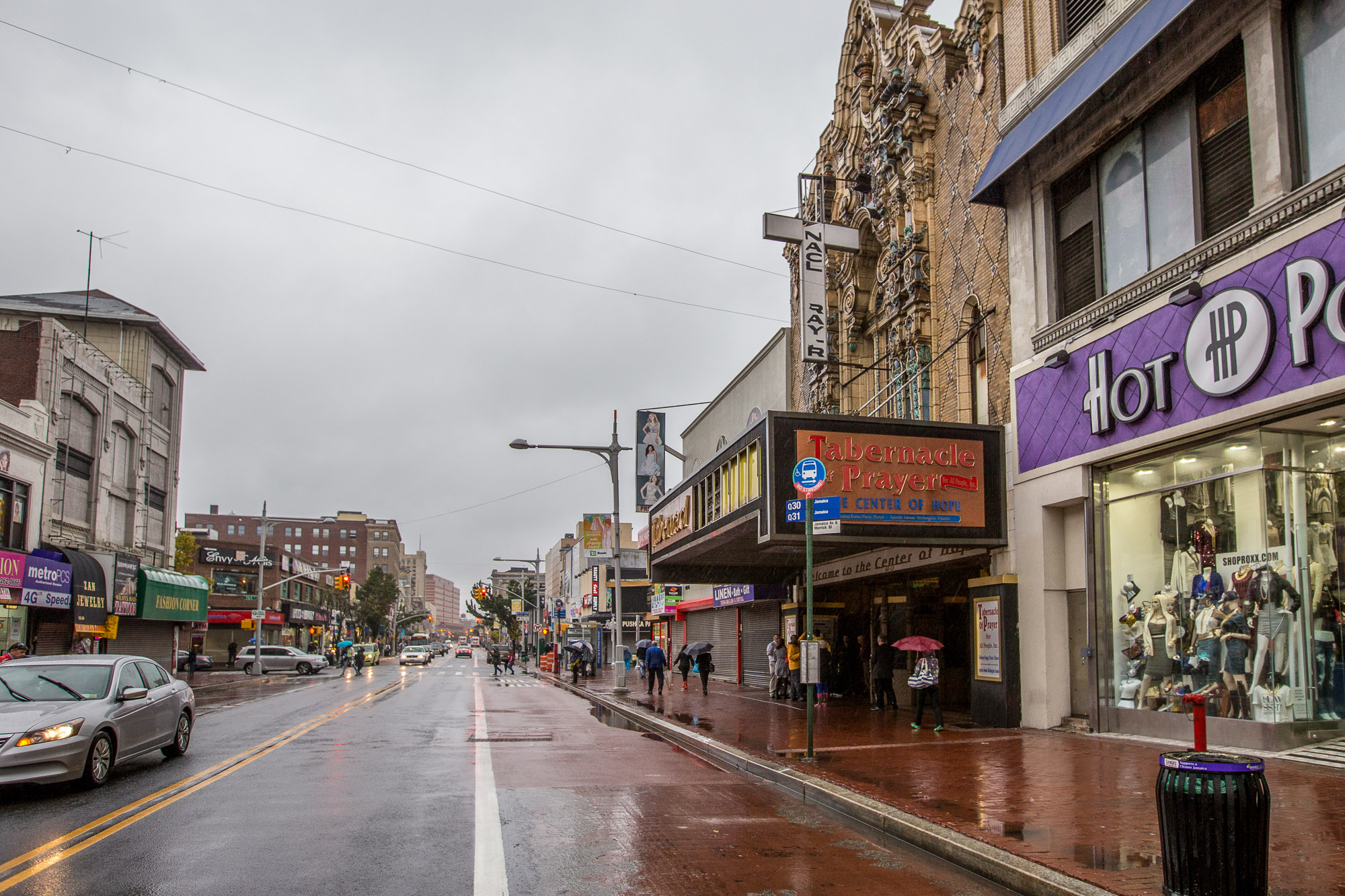 A street in Jamaica, Queens. The street is wet with rain. There are various stores and apartment buildings on both sides of the street.